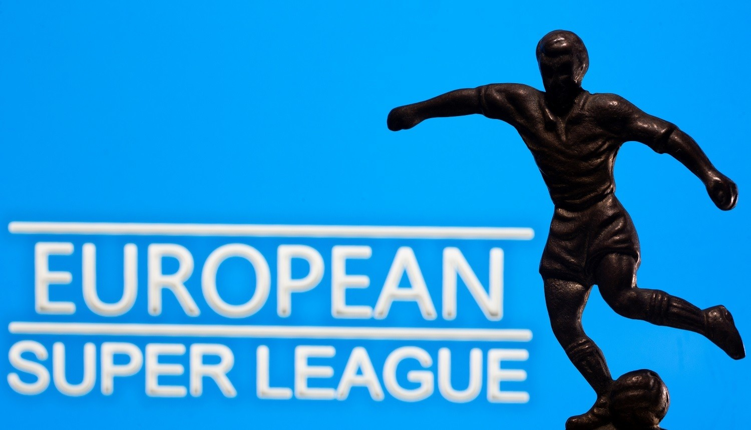 """A metal figure of a football player with a ball is seen in front of the words """"European Super League"""" in this illustration taken April 20, 2021. REUTERS/Dado Ruvic/Illustration - RC2QZM99RK4T"""