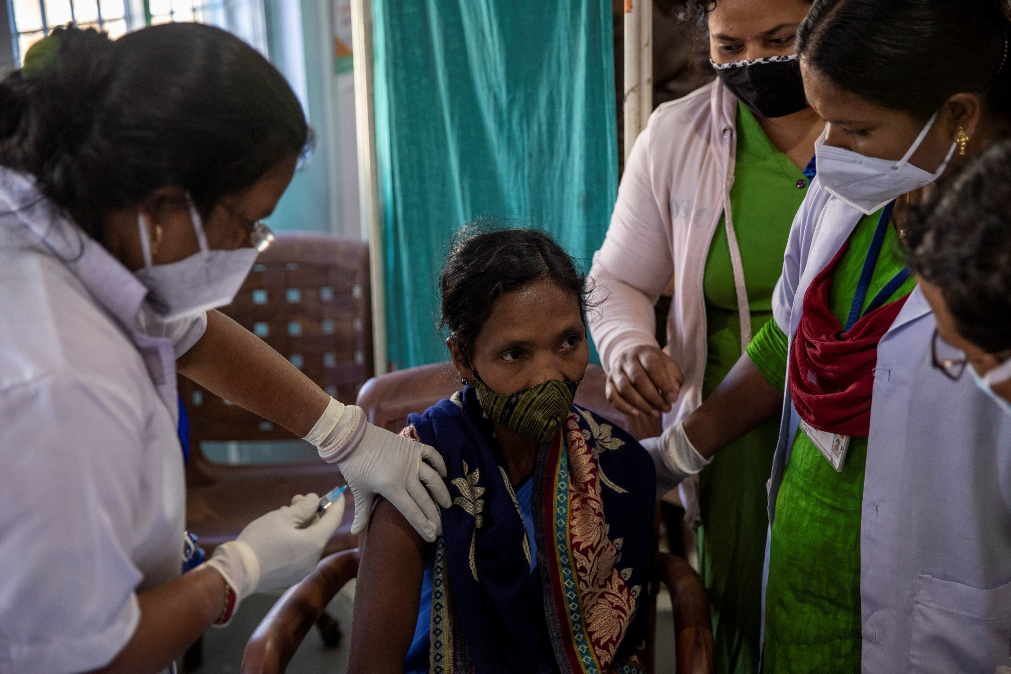 """Reena Jani, 34, a health worker, receives the vaccine developed by Oxford/AstraZeneca at Mathalput Community Health Centre, during the coronavirus disease (COVID-19) pandemic, in Koraput, India, January 16, 2021. Jani's name was on a list of 100 health workers at Mathalput Community Health Centre, making her one of the first Indians to be inoculated against COVID-19 earlier this month, as the country rolls out a vaccination programme the government calls the world's biggest. But she had heard rumours of serious side effects and worried about what would happen were she to get ill. """"I was frightened because of my son and daughters. If something happens to me, what will they do?"""" Jani said. REUTERS/Danish Siddiqui     SEARCH """"SIDDIQUI OXFORD/ASTRAZENECA"""" FOR THIS STORY. SEARCH """"WIDER IMAGE"""" FOR ALL STORIES. TPX IMAGES OF THE DAY. - RC2SEL9ODK0Y"""