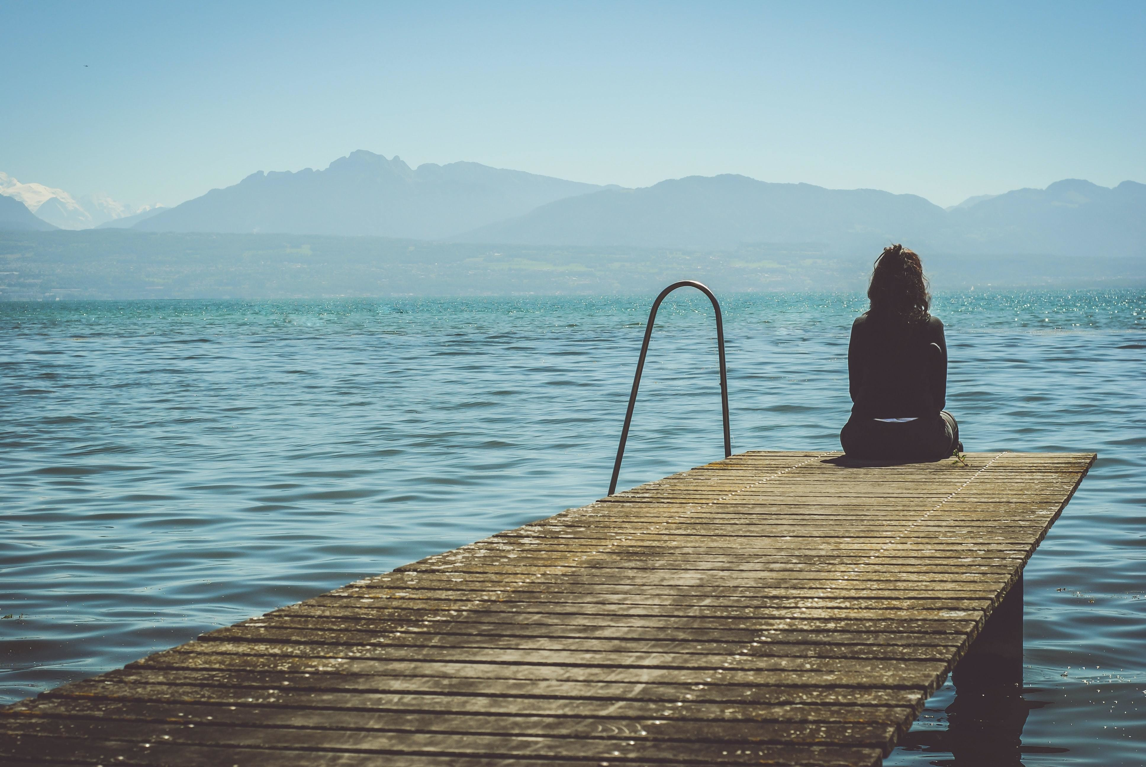 A woman sitting at a dock, looking at the water.