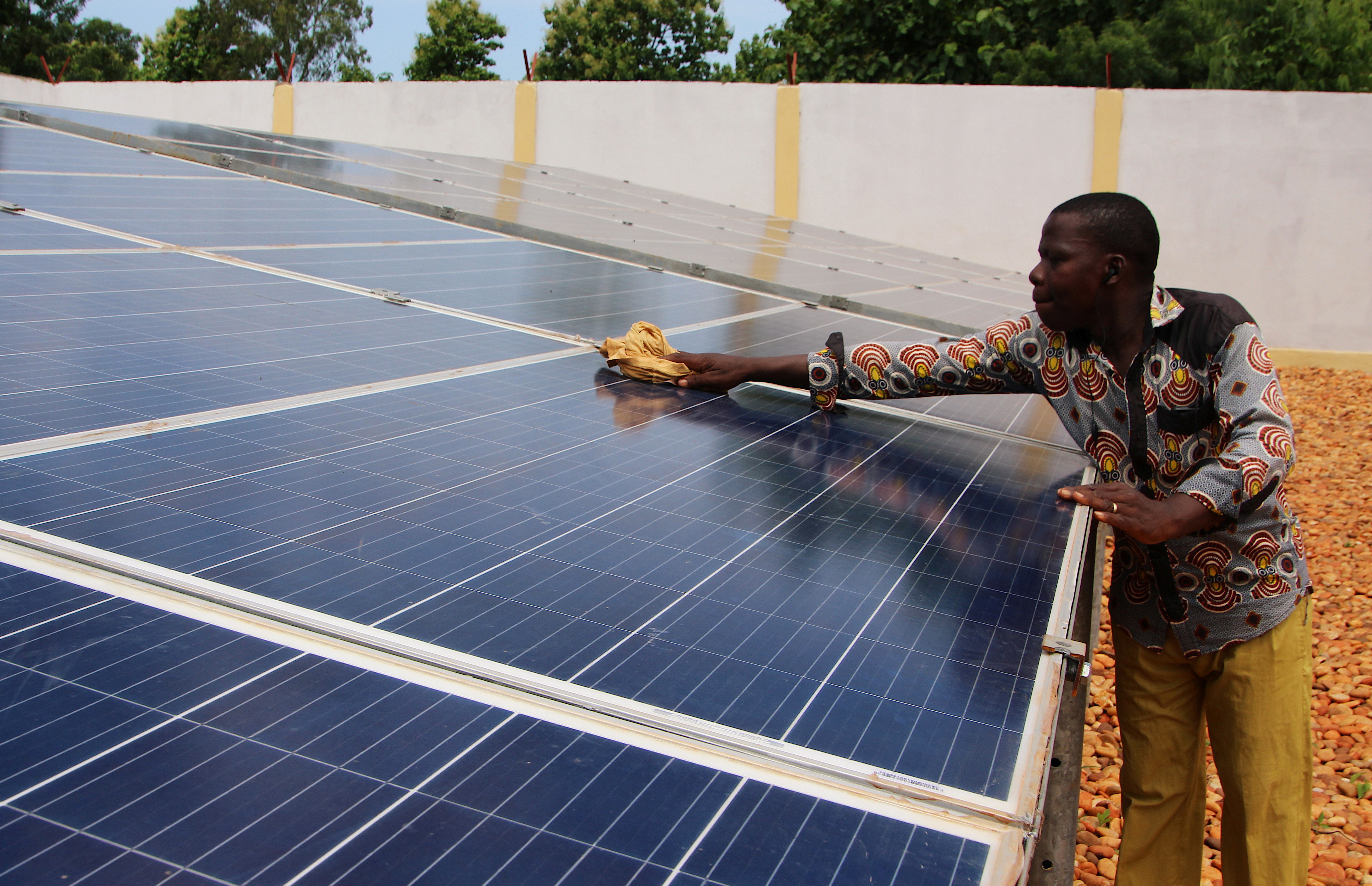 A technician cleans solar panels, part of the BBOXX and EDF solar energy system used to provide electricity to Sikpe Afidegnon village, Togo May 16, 2019. Picture taken May 16, 2019. REUTERS/Noel Kokou Tadegnon - RC123FE24560