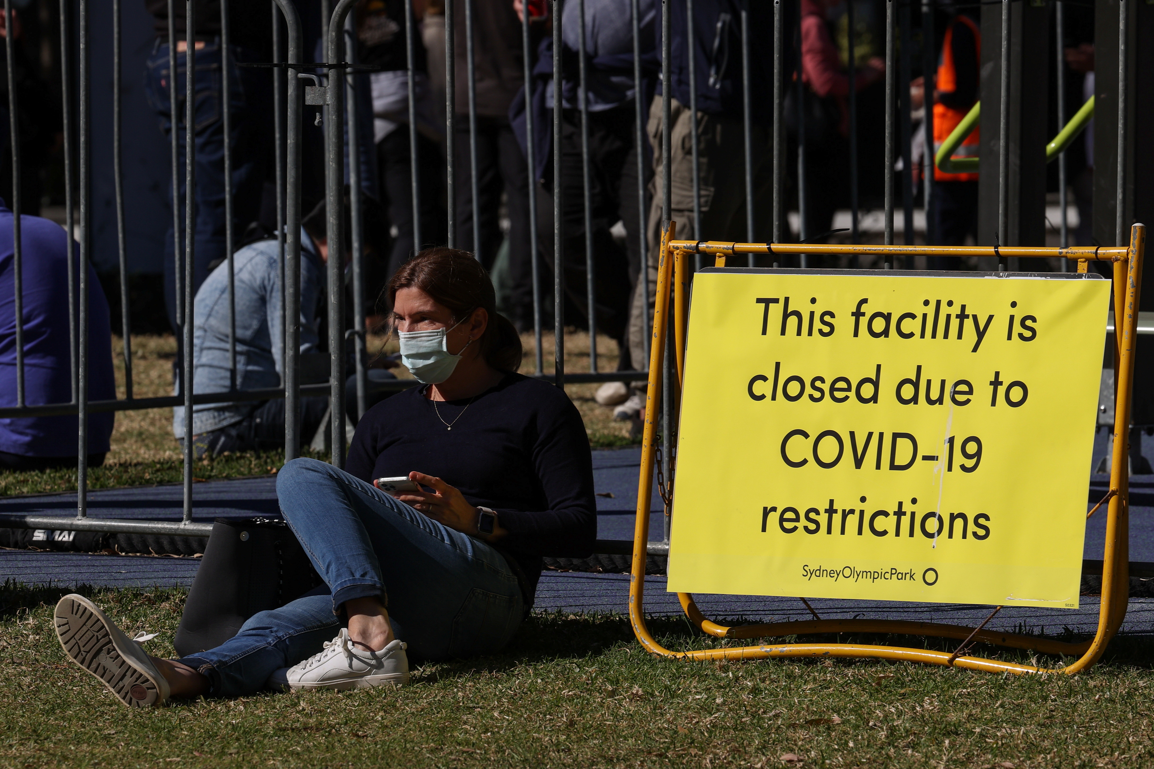 People spread out in a park while waiting for their appointments outside a coronavirus disease (COVID-19) vaccination centre at Sydney Olympic Park during a lockdown to curb the spread of an outbreak in Sydney, Australia, August 16, 2021.  REUTERS/Loren Elliott - RC226P9Z4ECE