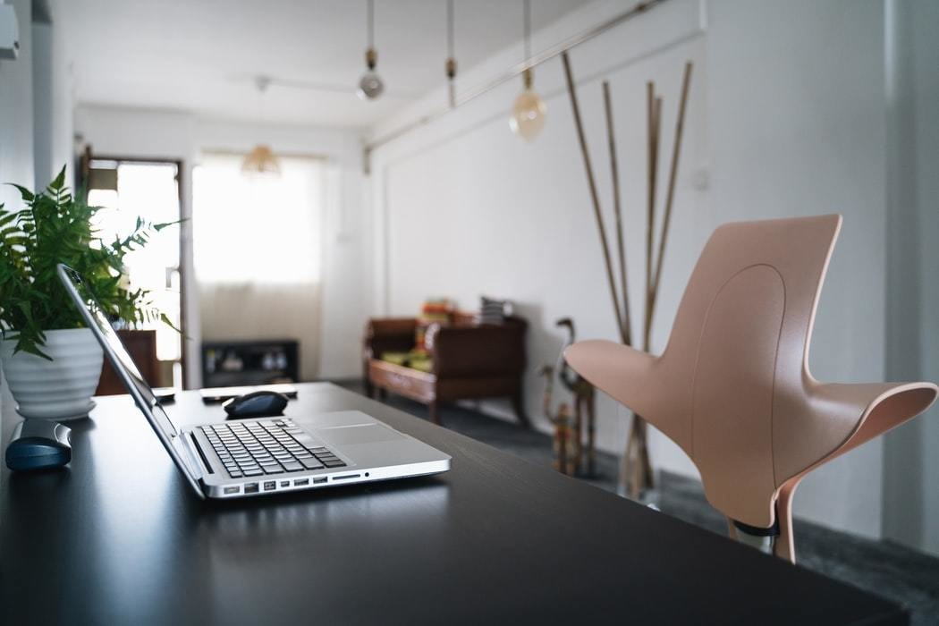 A home office, occupied by a laptop and chair.