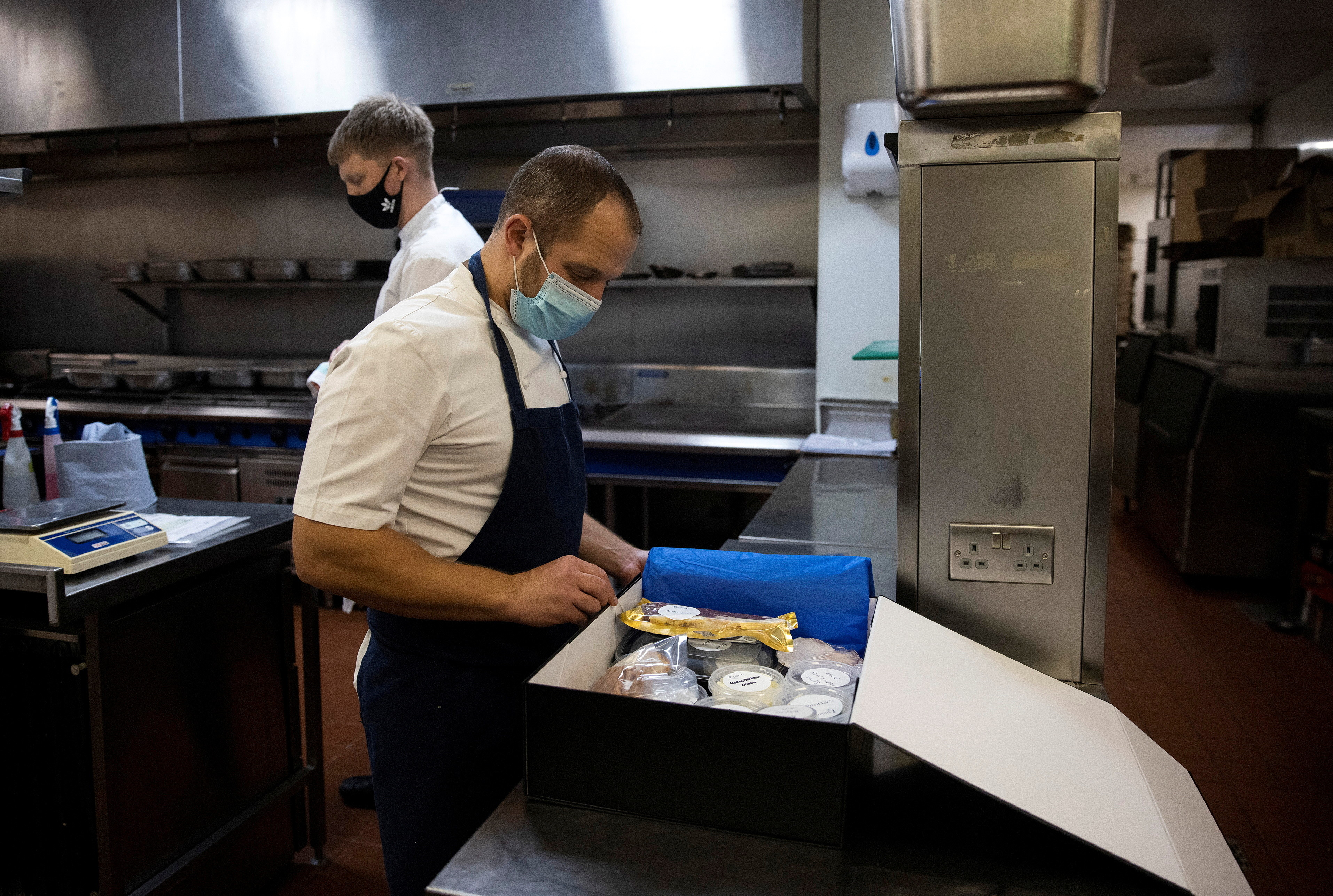 James Knappett, founder and head chef of 'Home', the first at-home fine dining experience, packs food into a box destined for customers in London, Britain, November 18, 2020. Picture taken November 18, 2020. REUTERS/Simon Dawson - RC2BAK9QVT5C