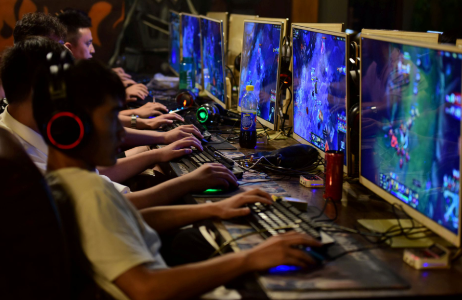 people play online games at an internet cafe in Fuyang, Anhui province, China