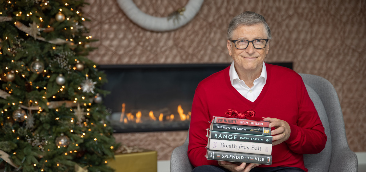 Bill Gates sits by a christmas tree with a stack of five books in his hand