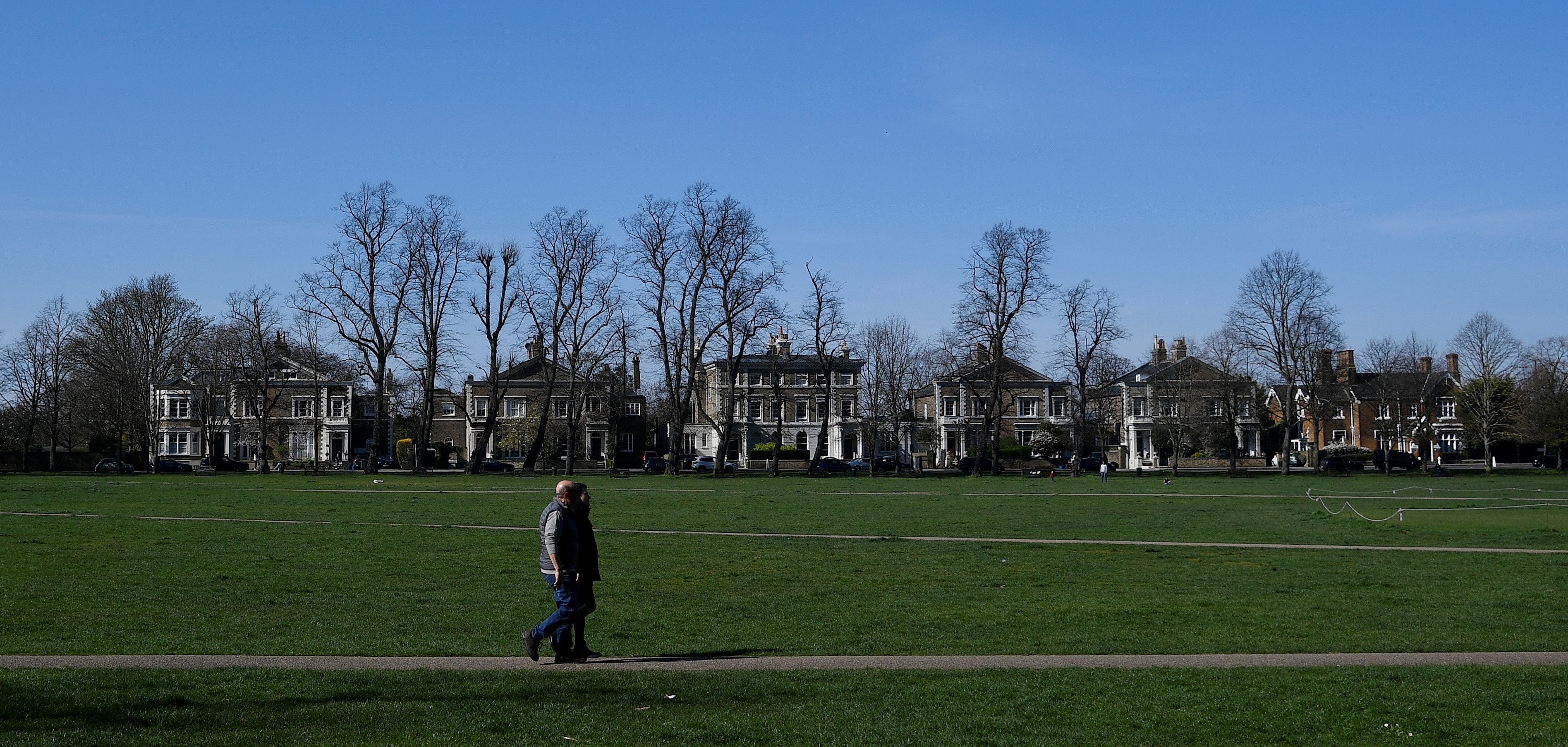 People walk across Richmond Green public space in Richmond South West London as the spread of the coronavirus disease (COVID-19) continues, in London, Britain, March 24, 2020. REUTERS/Toby Melville - RC2EQF9EX9Y4