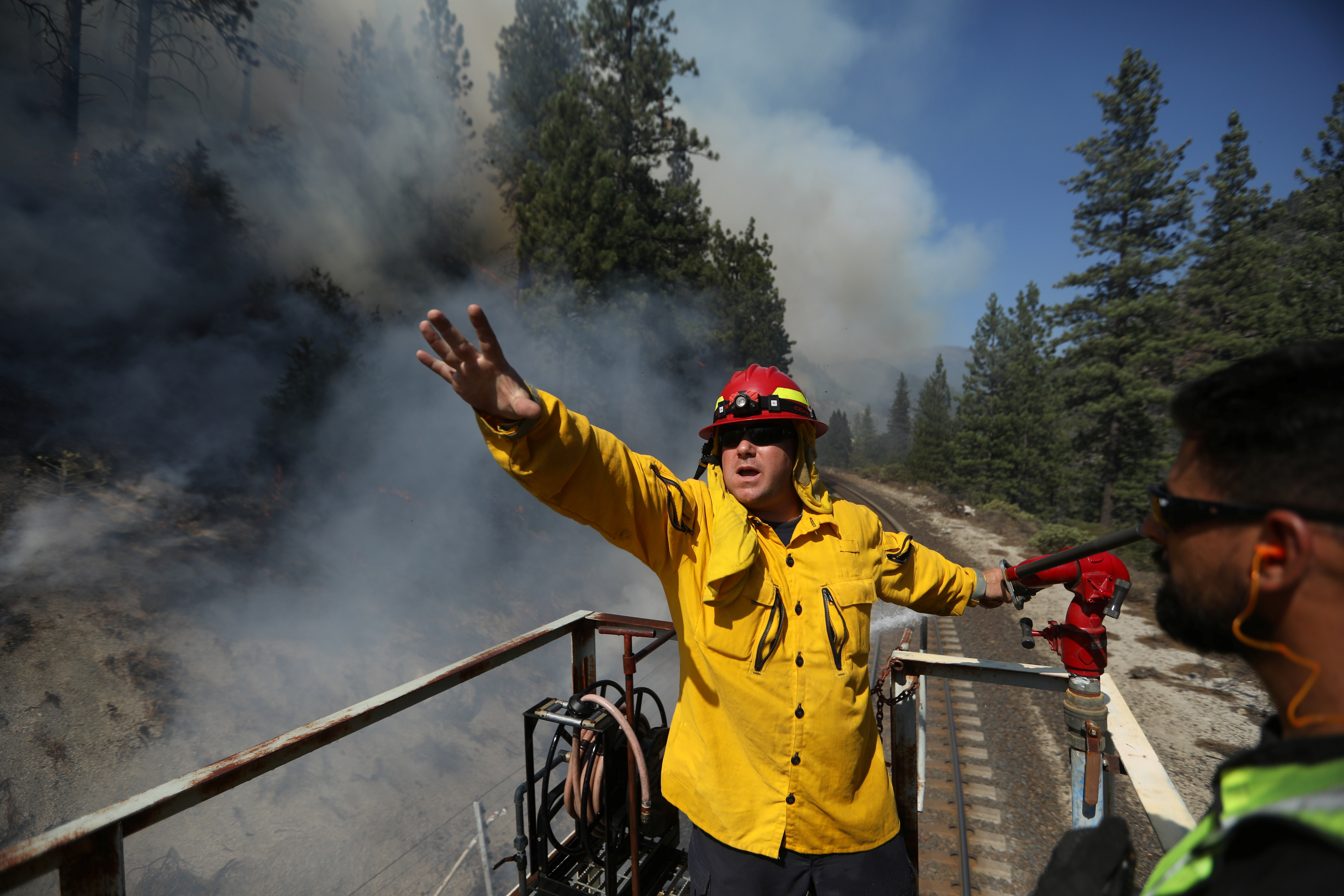 a firefighter shouts  orders while fighting a wildfire