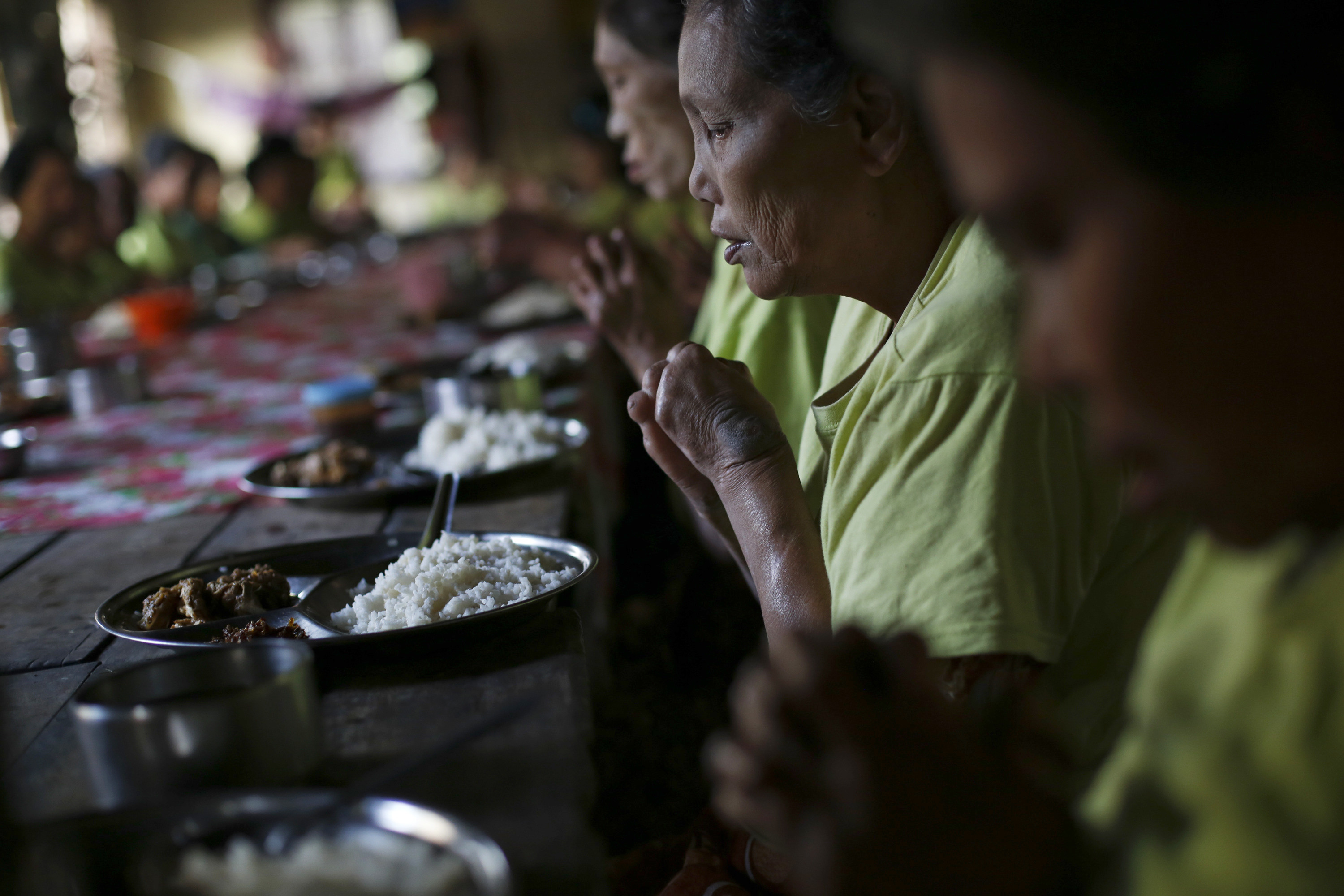Patients pray for donors before they eat their meal at Mayanchaung Leprosy Hospice, Halegu township. Yangon Division January 21, 2014. The hospice was founded in 1989 and houses 118 people. About 3,000 people are newly diagnosed with leprosy in Myanmar every year and about 300,000 people have been cured of the disease since 1991, according to the Myanmar Leprosy Mission. Picture taken January 21, 2014.