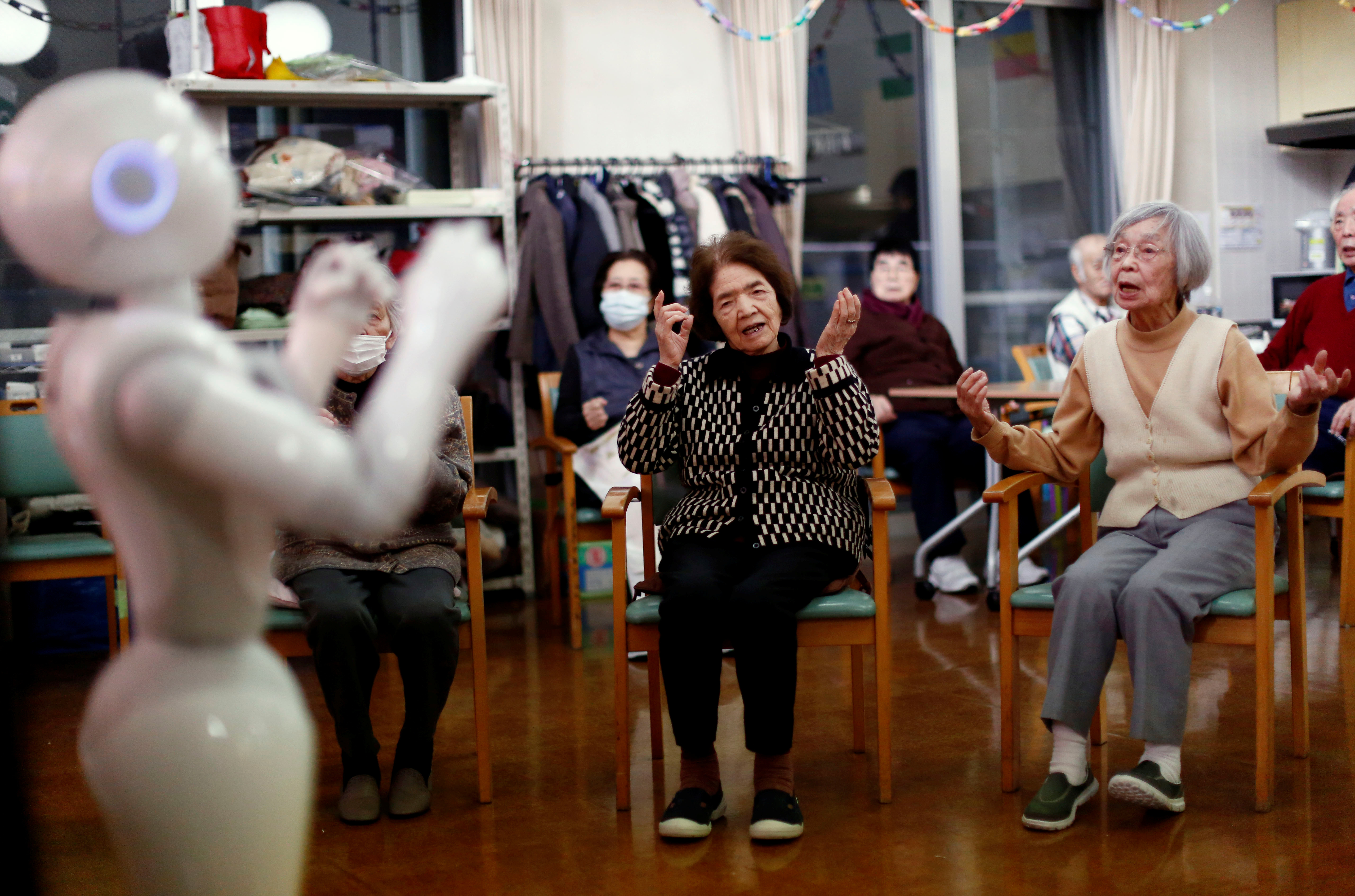 Residents follow moves made by humanoid robot 'Pepper' during an afternoon exercise session at a nursing home in Tokyo.