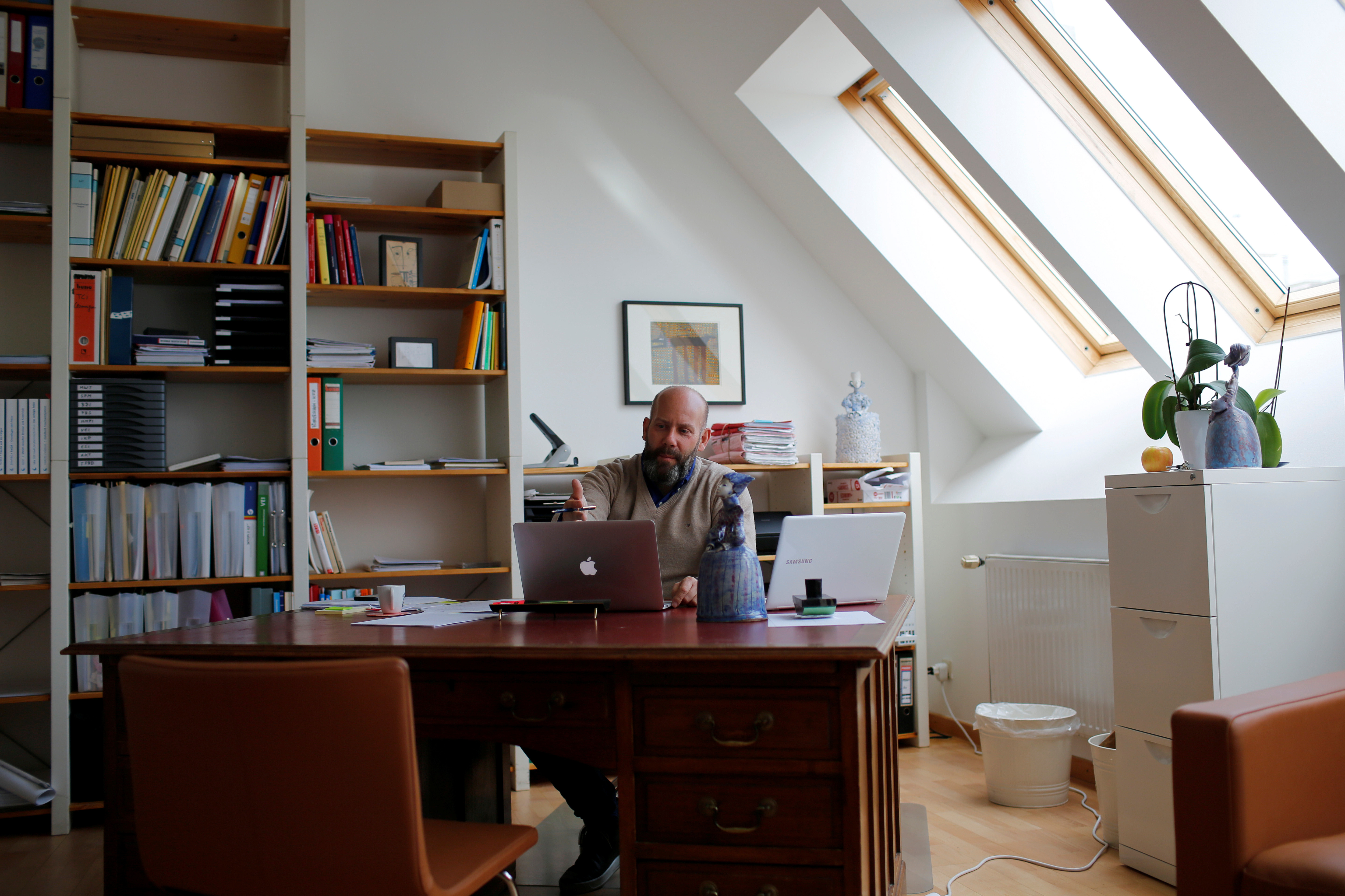 Self-employed psychologist Wolfgang Neuwirth gestures in front of a laptop inside his office.