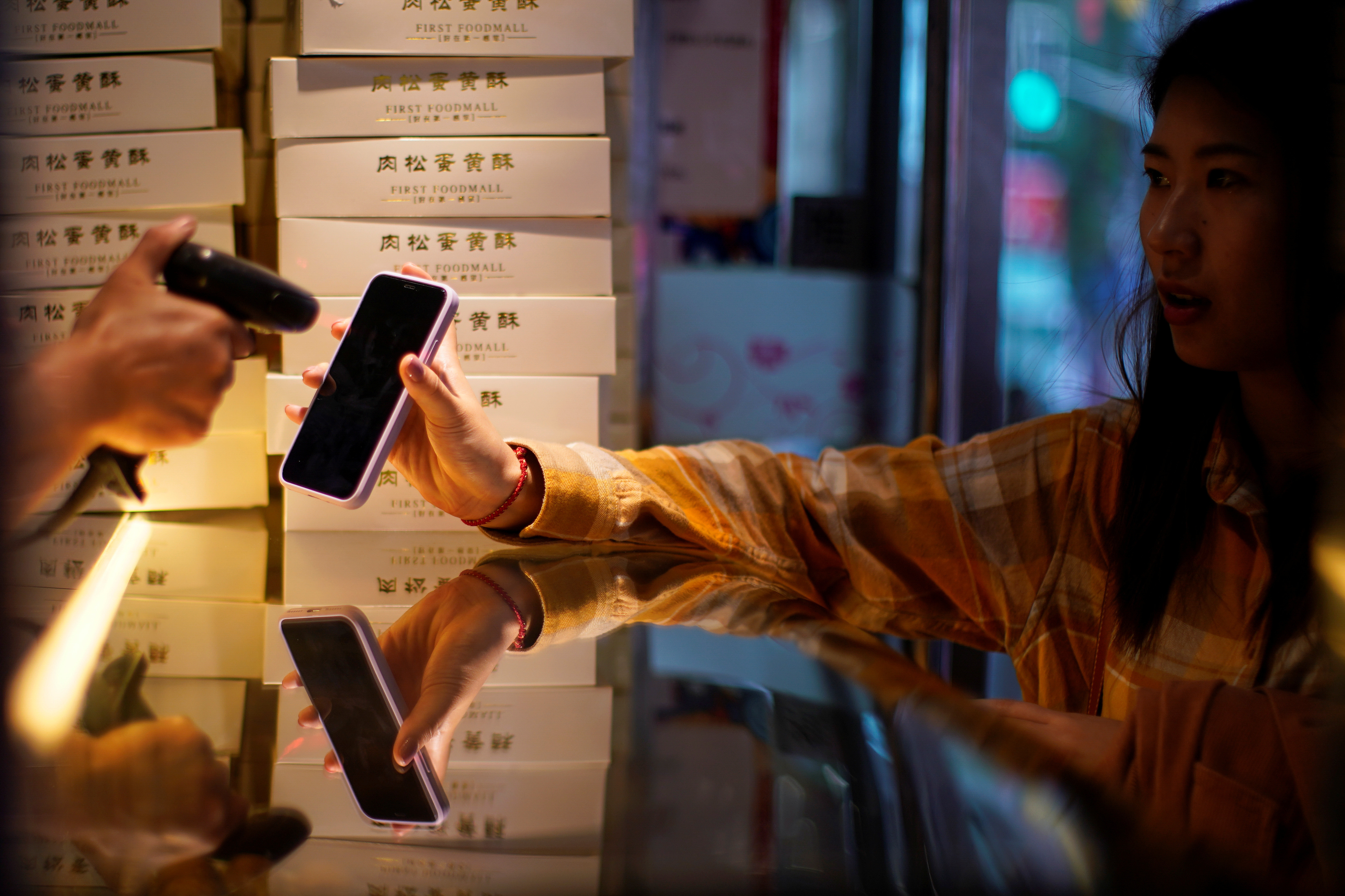 A woman gets her phone's QR code of the digital payment services scanned at a food shop, following the coronavirus disease (COVID-19) outbreak, in Shanghai, China October 10, 2020. REUTERS/Aly Song - RC2MFJ9WRM74