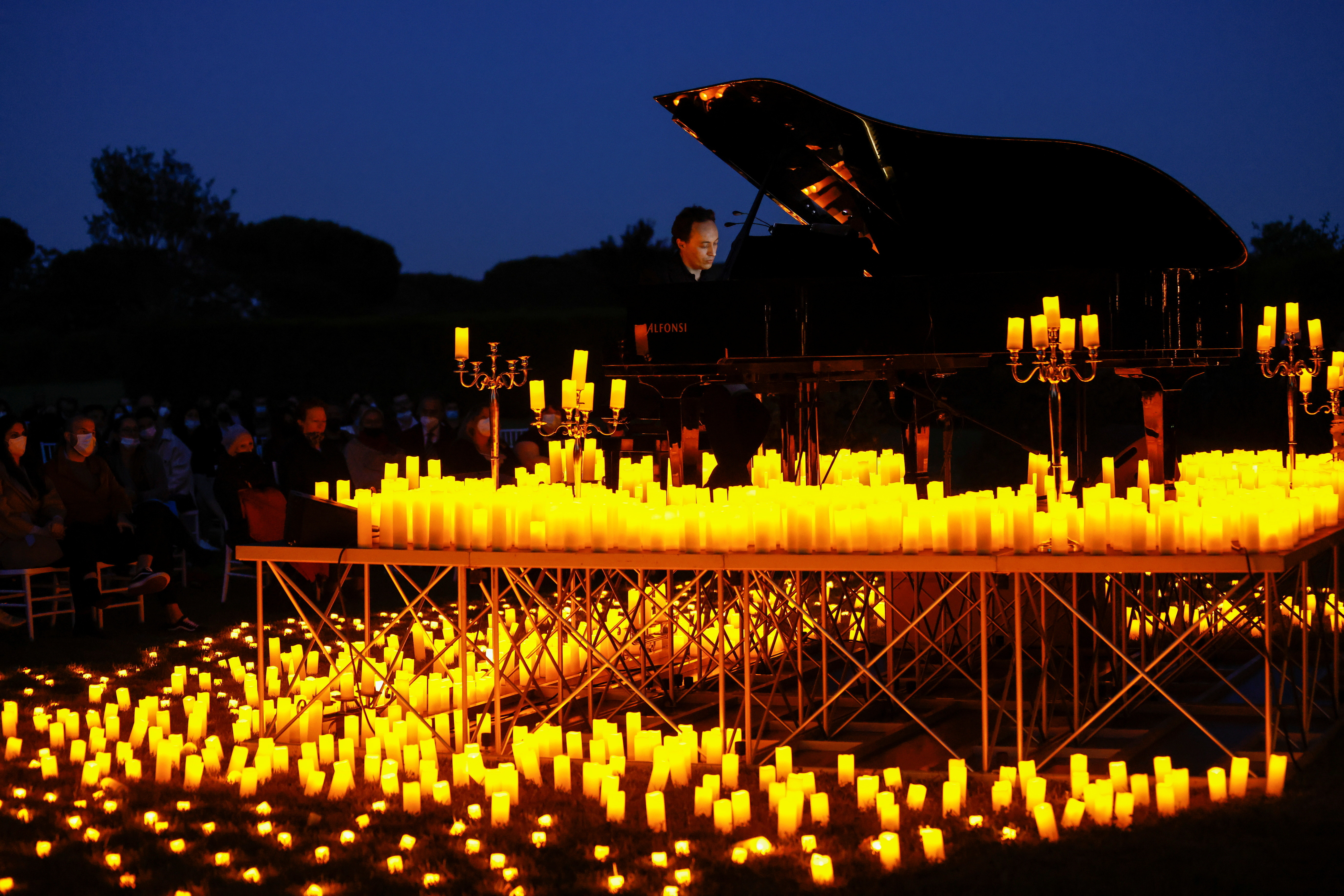 Pianist Giuseppe Califano plays during a candlelight concert inside the archaeological park of Appia Antica, during the coronavirus disease (COVID-19) pandemic, in Rome, Italy, May 10, 2021.