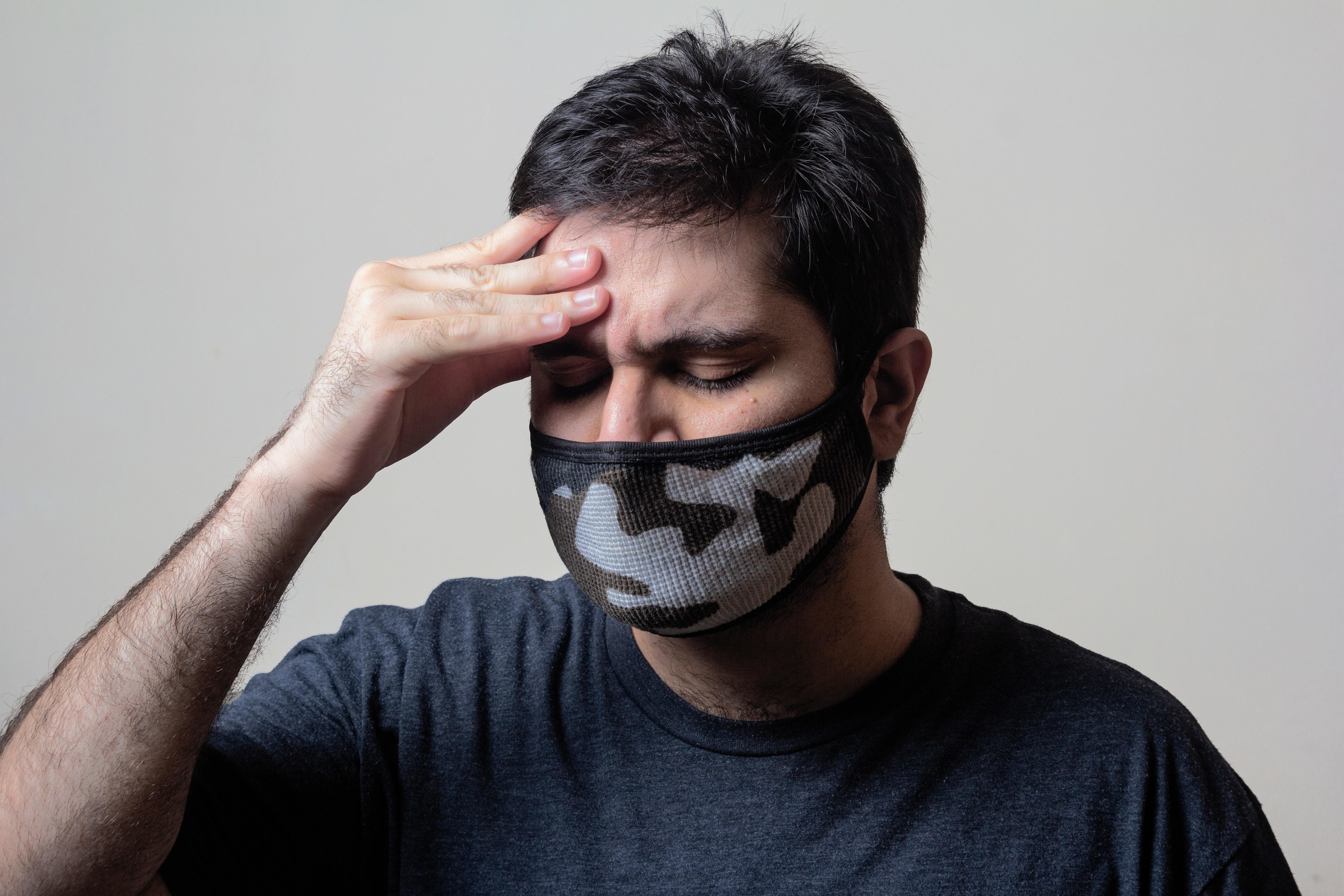 image of an anxious-looking man wearing a COVID-19 mask