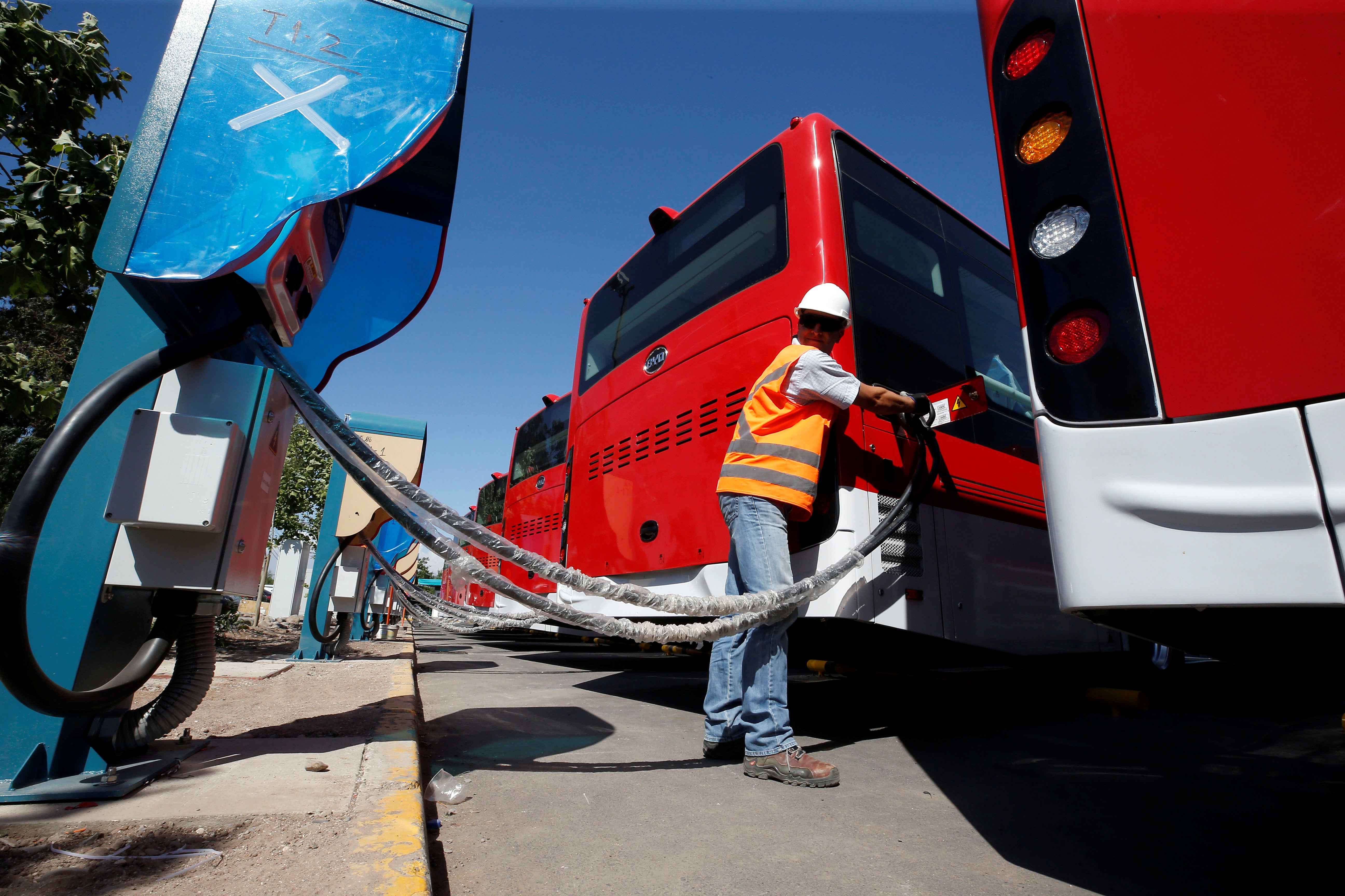 A man plugs an electric bus, manufactured by China's BYD, as part of the new fleet of electric buses for public transport in Santiago, Chile  November 28, 2018. Picture taken November 28, 2018