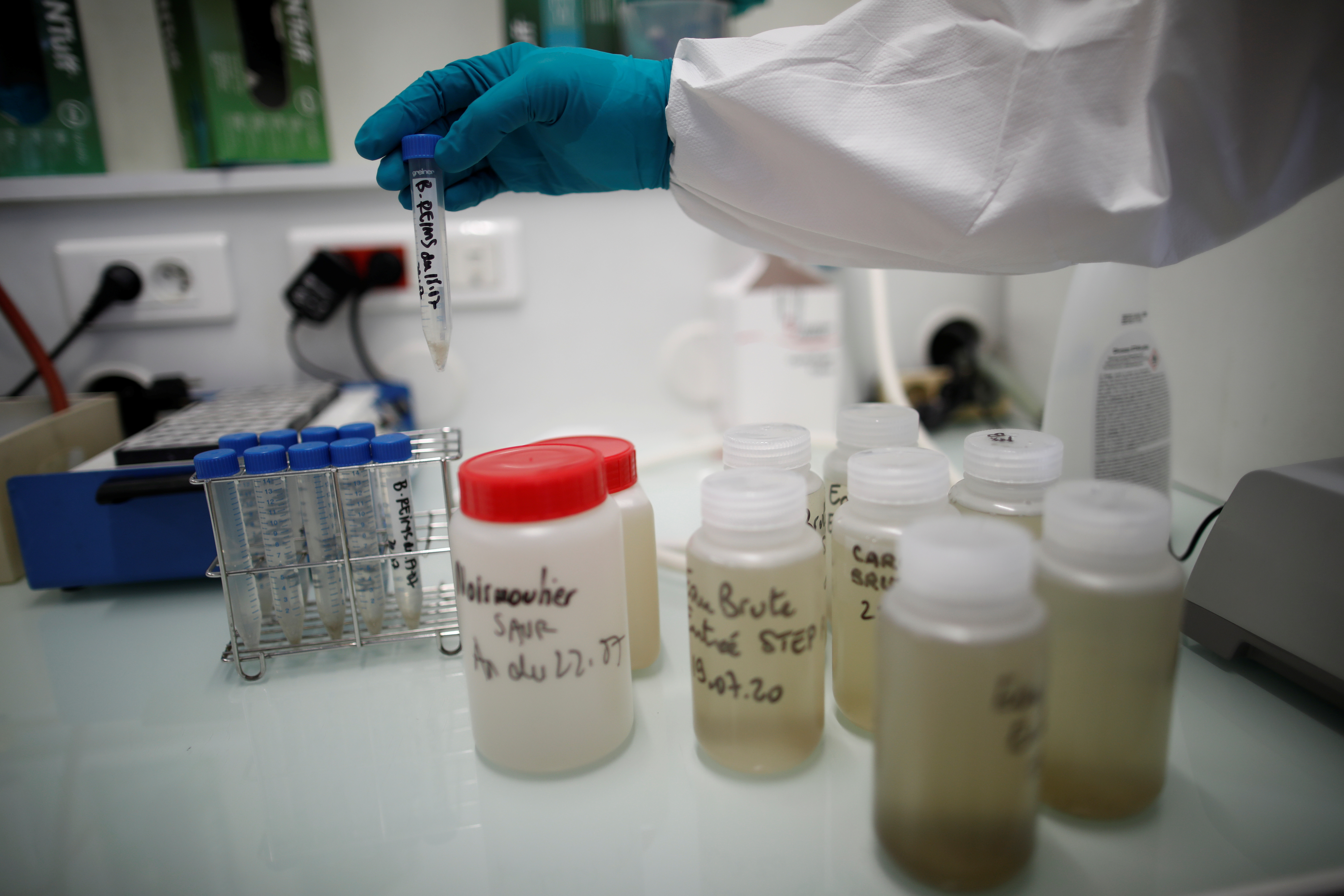 A water quality scientist holds a water sample at the Eau de Paris research and analysis laboratories in Ivry-sur-Seine, near Paris, France, July 22, 2020. Scientists study the Paris waste water to detect the concentration of COVID-19 traces as France remains vigilant against the spread of the coronavirus disease. Picture taken July 22, 2020. REUTERS/Benoit Tessier - RC2ZYH9PJCYY