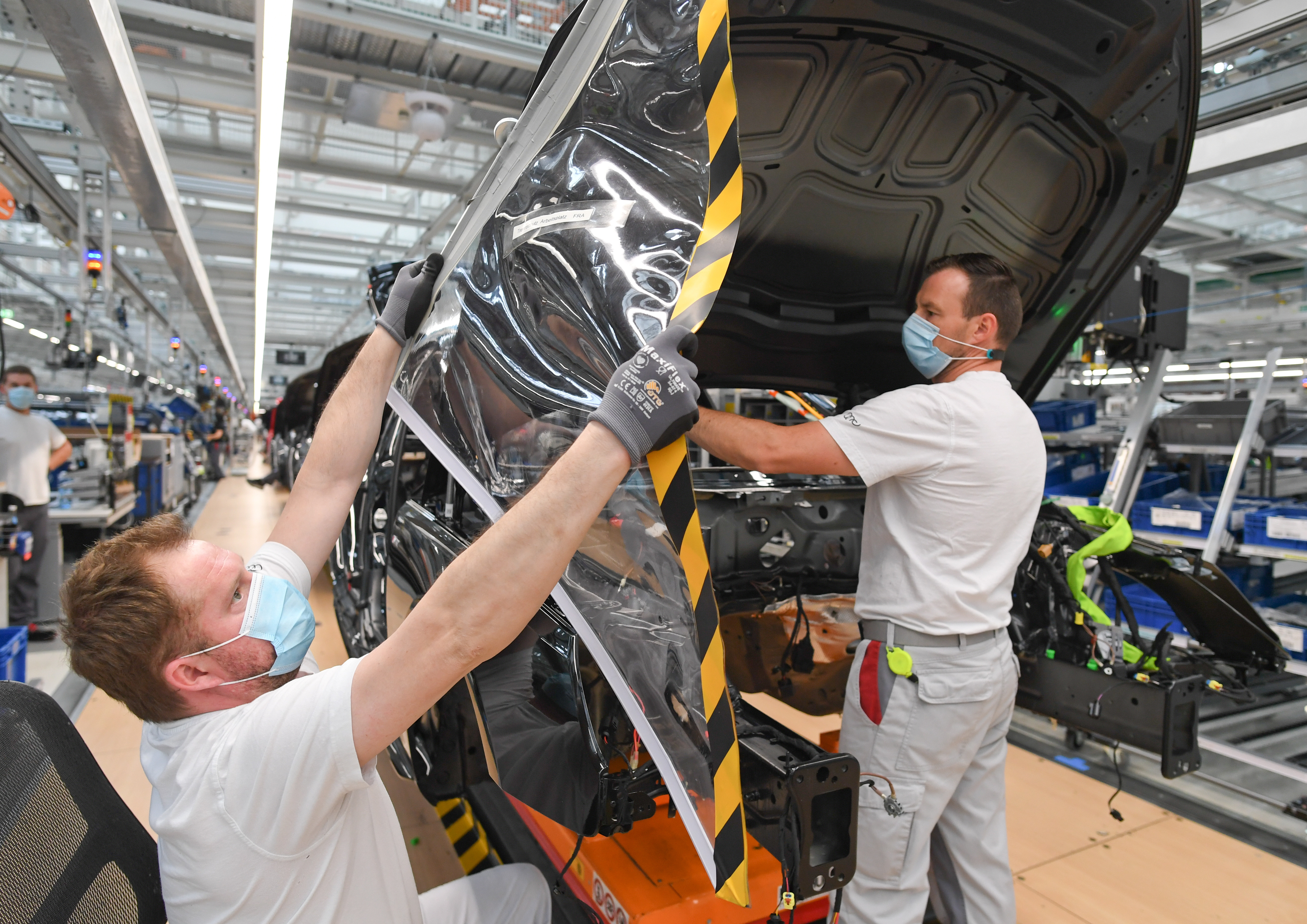 image of two employees, separated by plastic hygiene protection, working in car manufacturing during COVID-19