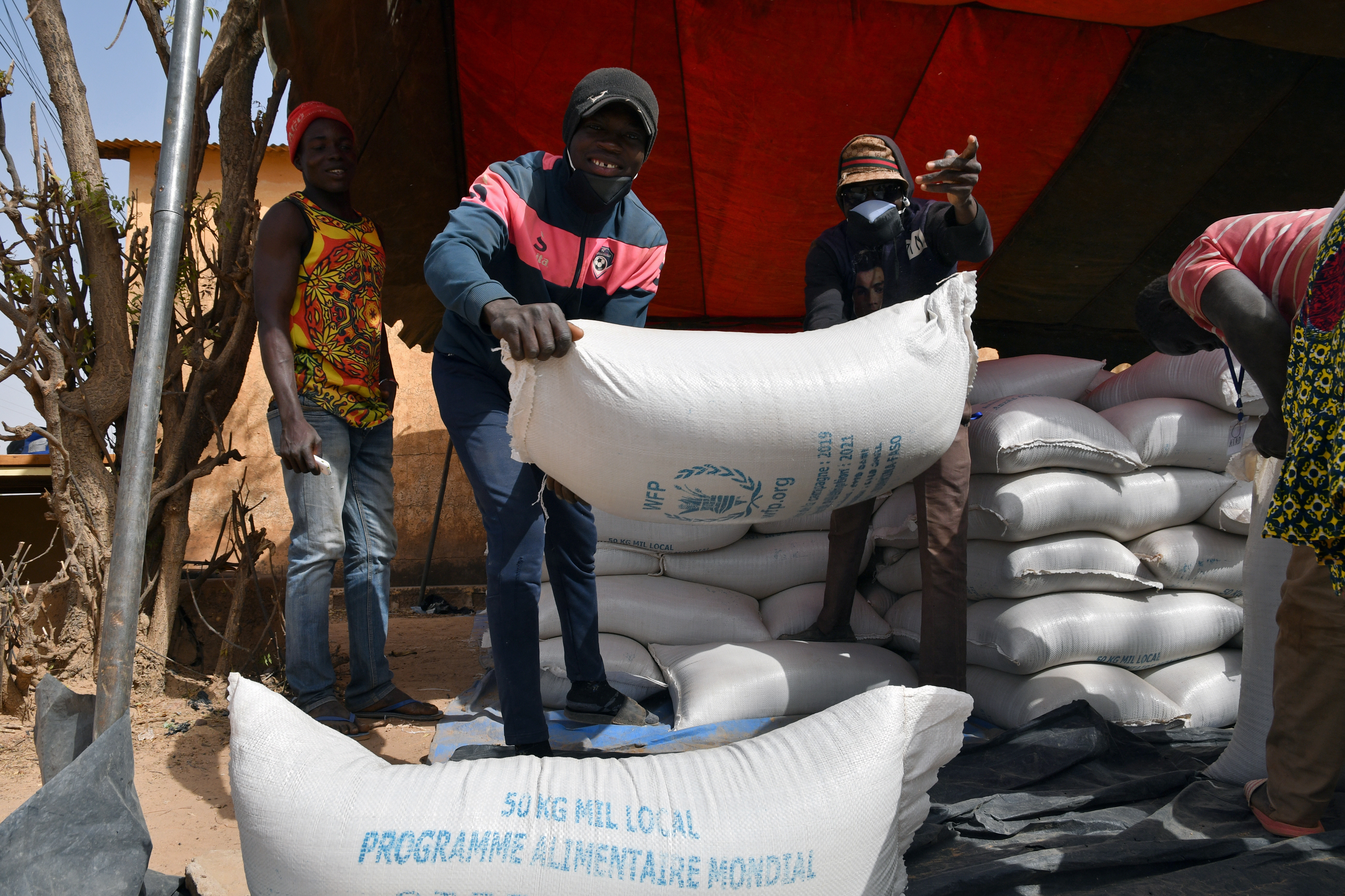 Workers carry the aid provided by the World Food Programme (WFP) for distribution in Pissila, Burkina Faso January 24, 2020. Picture taken January 24, 2020. REUTERS/Anne Mimault - RC21PE9DV74I