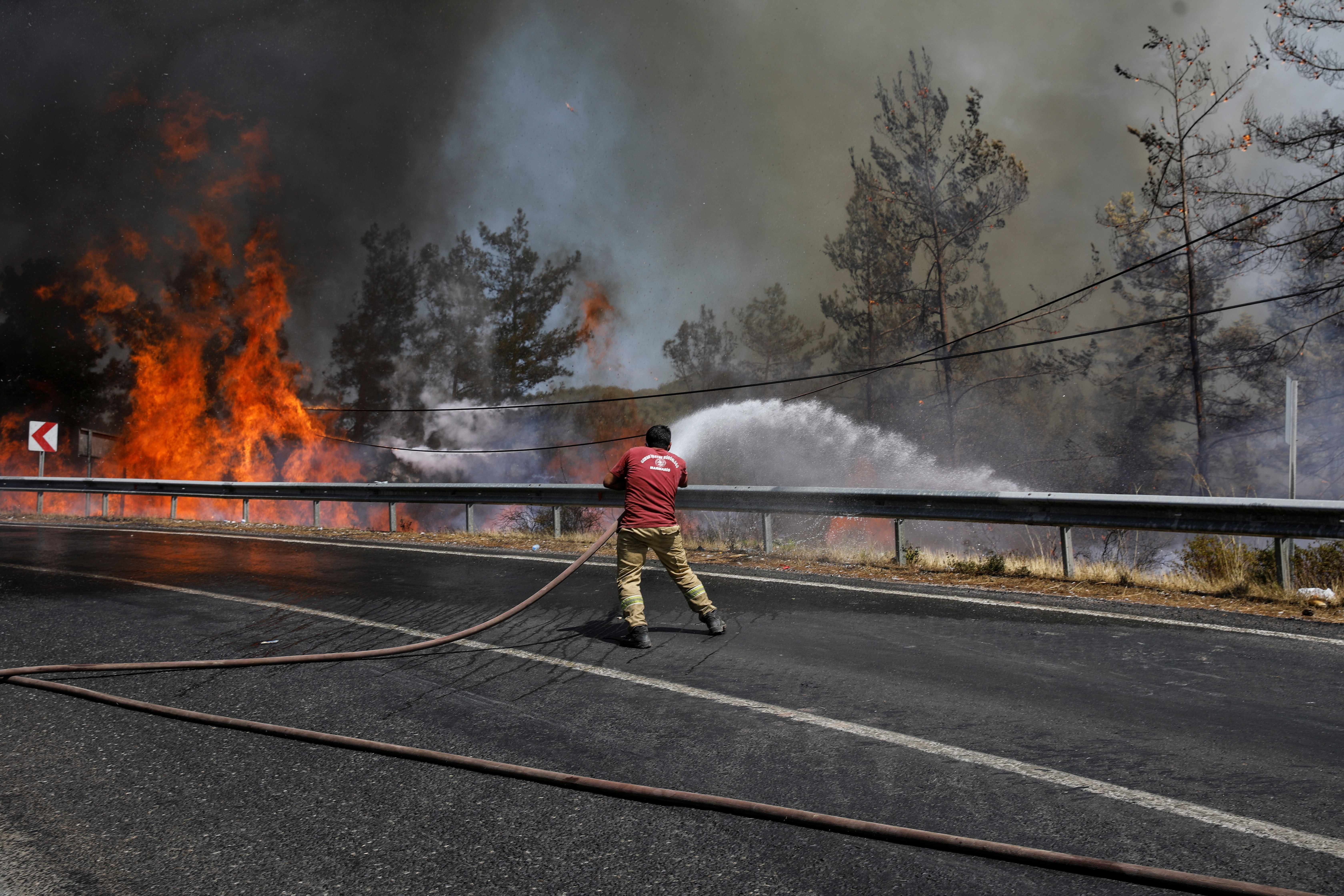 A firefighter tries to extinguish a wildfire near Marmaris, Turkey, August 1, 2021.
