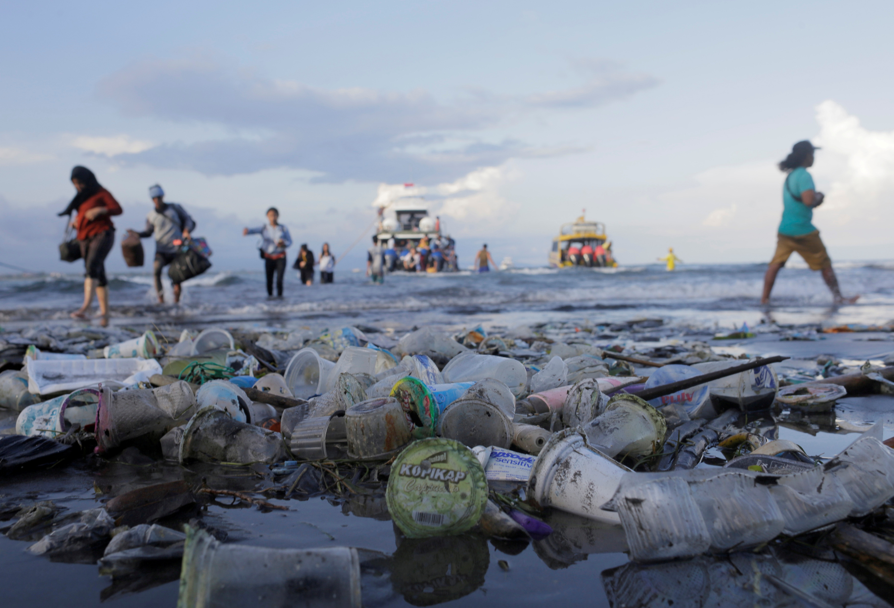 people pick up plastic on a beach