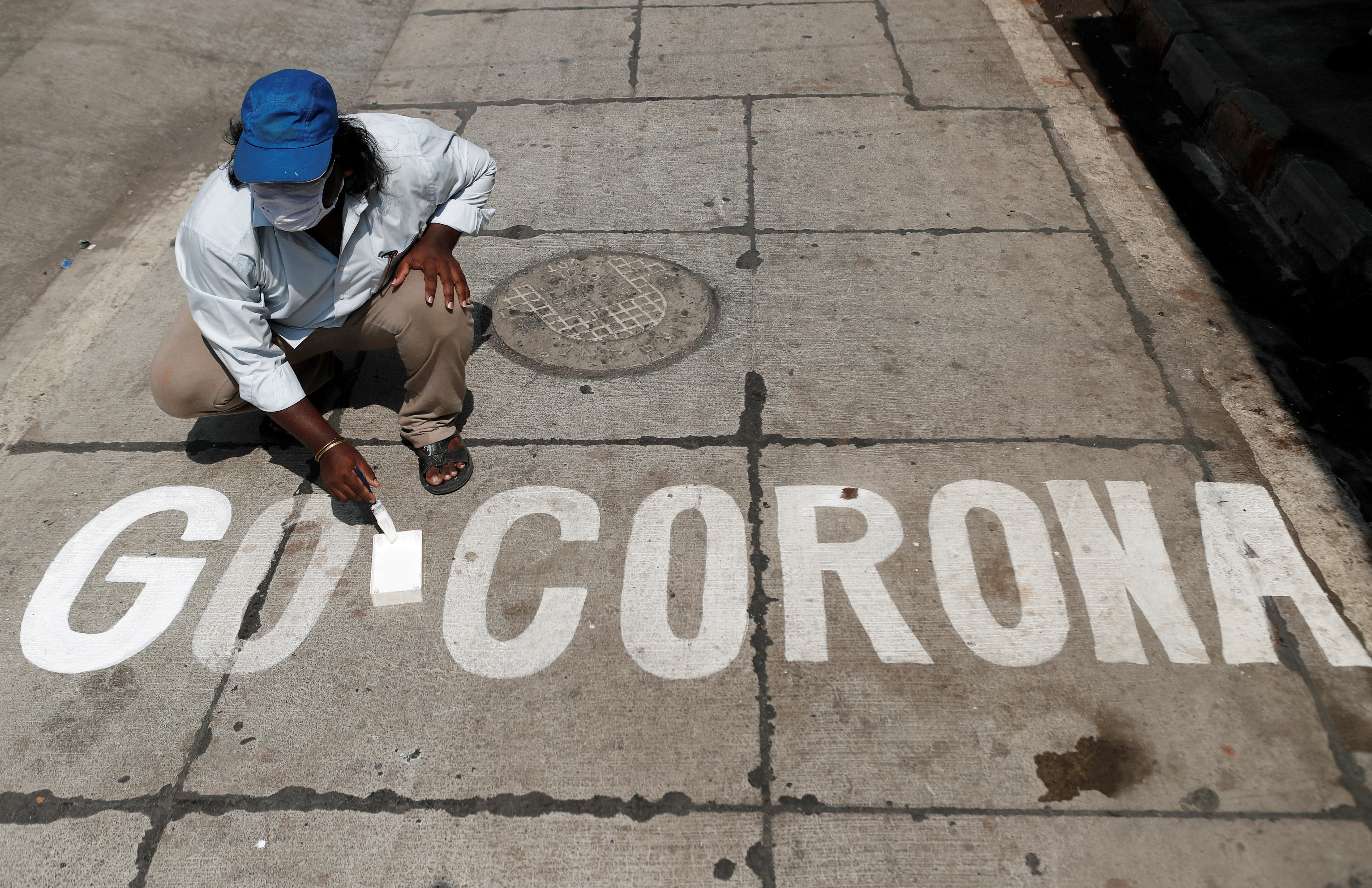 A man paints a message on a street after India ordered a 21- day nationwide lockdown to limit the spreading of coronavirus disease (COVID-19) in Mumbai, India March 28, 2020. REUTERS/Francis Mascarenhas     TPX IMAGES OF THE DAY - RC2YSF9BHTFJ