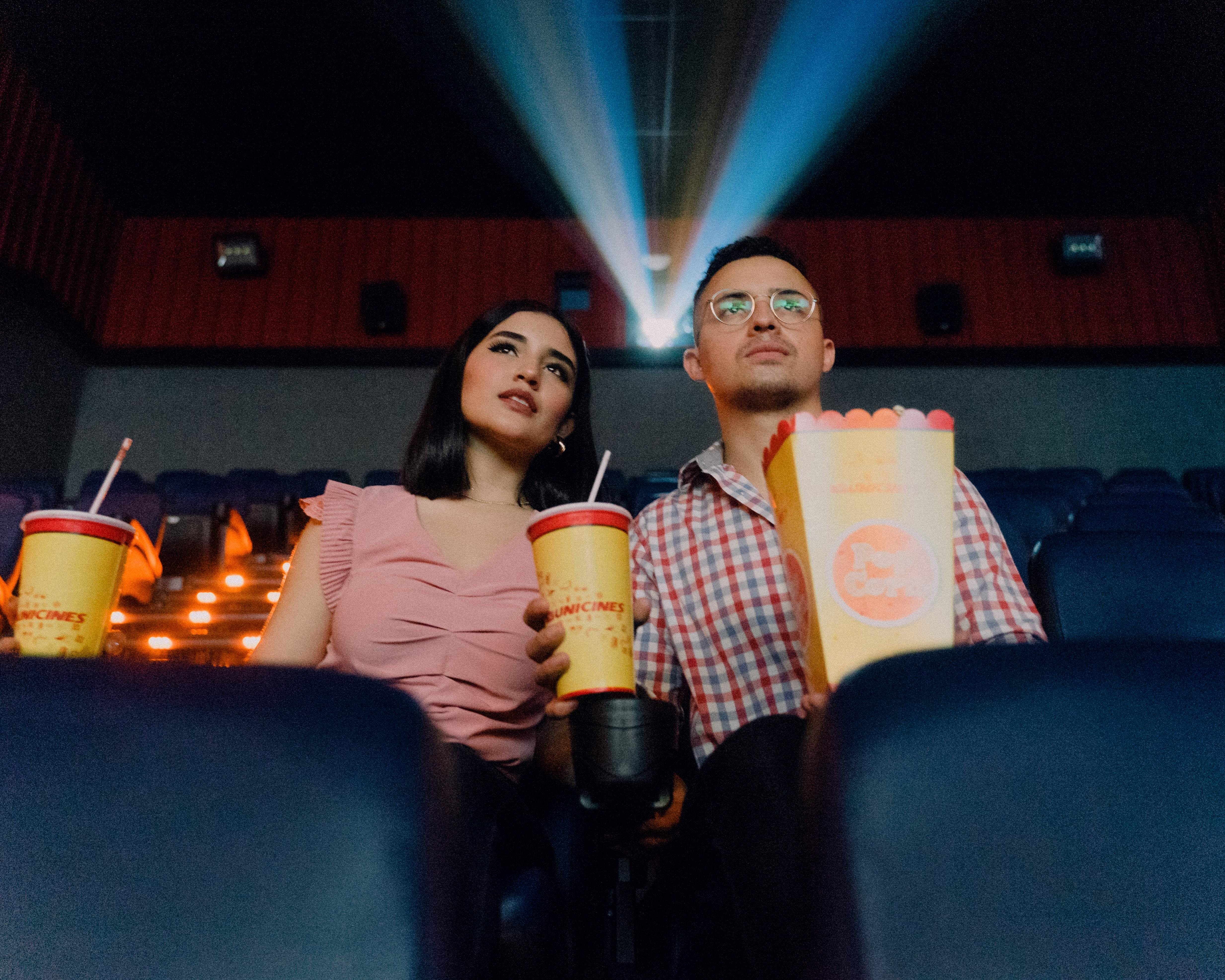 this couple are sitting in a cinema watching a film