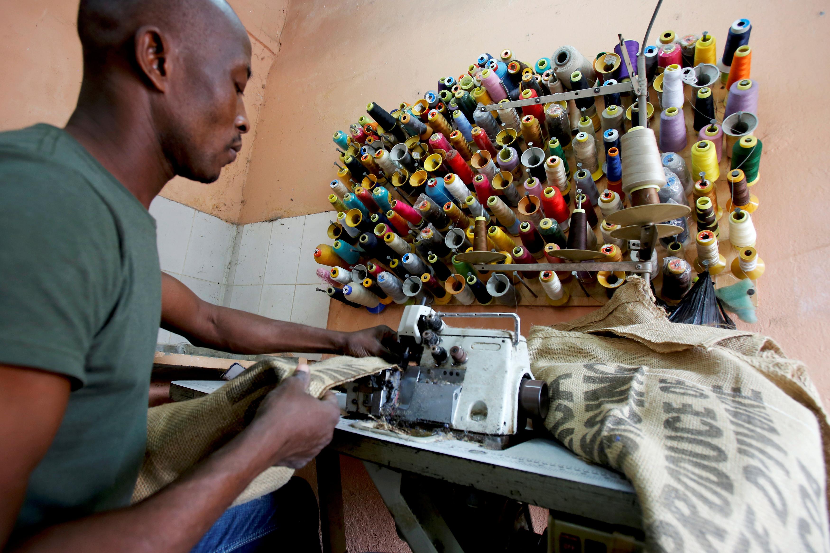 A man works on a sewing machine inside the workshop of Ivory coast fashion designer Liliane Estievenart, 45, in Abidjan, Ivory Coast July 22, 2017. Picture taken July 22, 2017. REUTERS/Thierry Gouegnon - RC151B9D8610