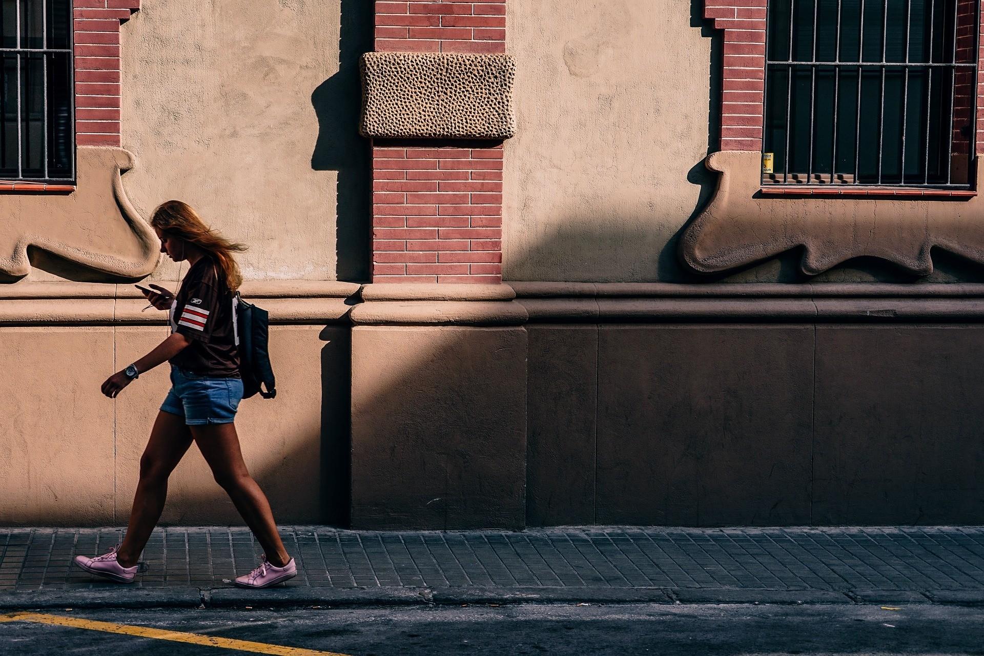Women walking while looking at phone