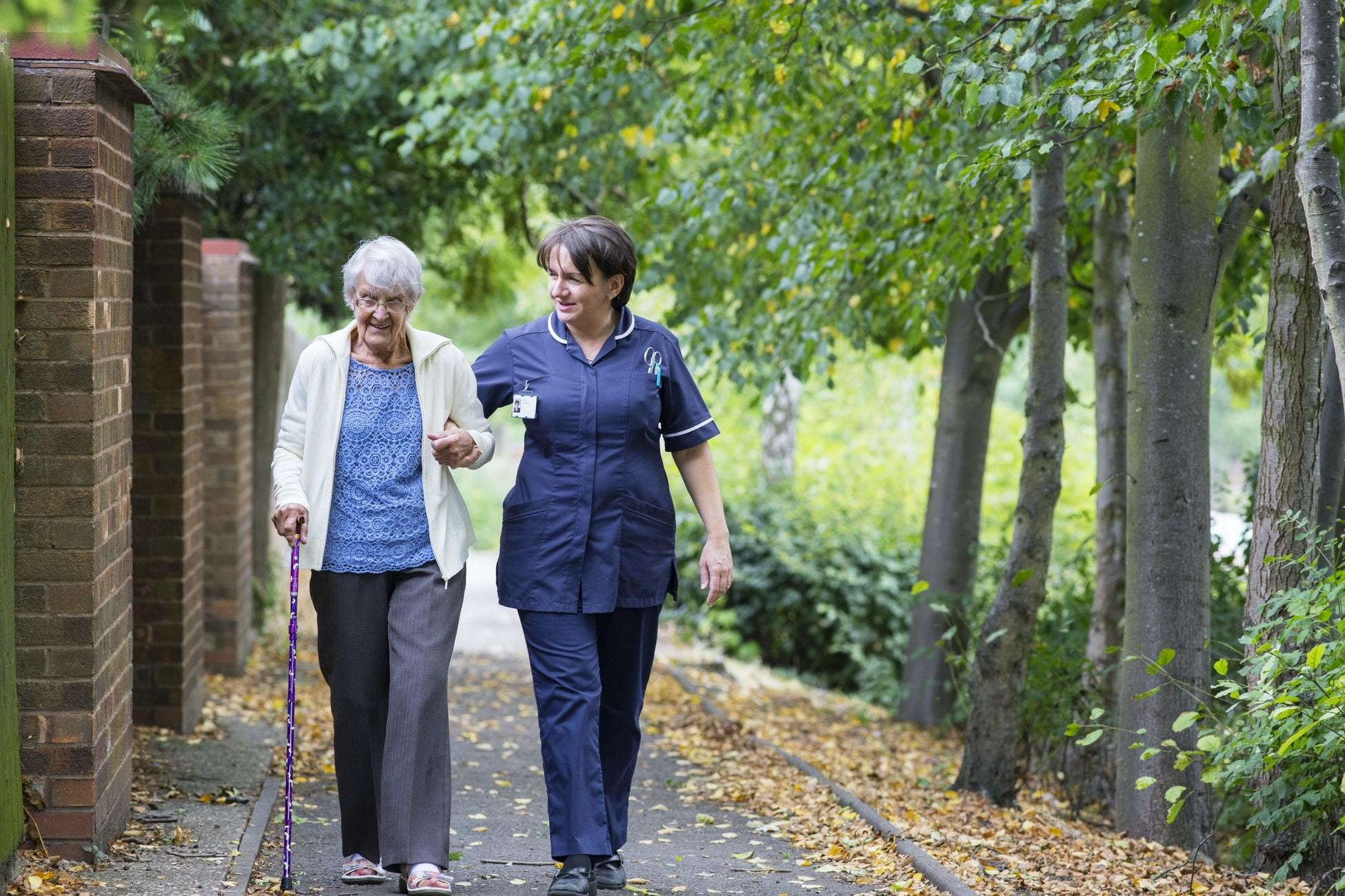 image of a care worker walking with an elderly lady