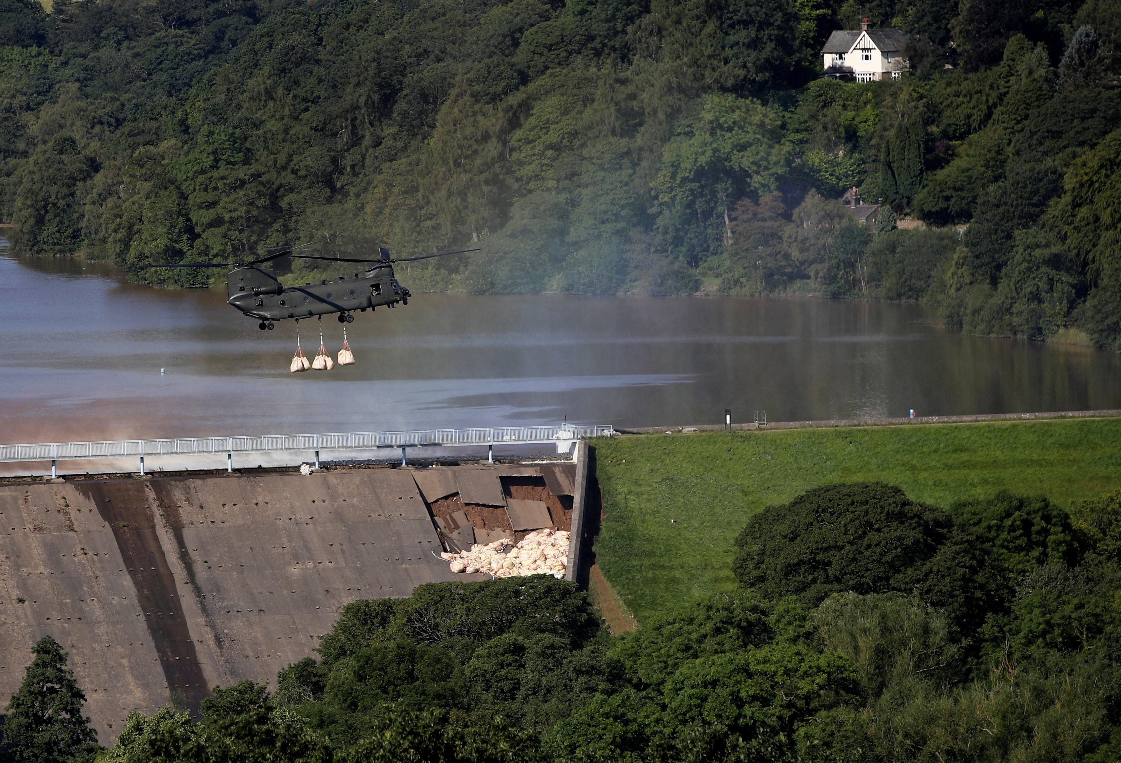A helicopter drops sand bags on top of the dam after a nearby reservoir was damaged by flooding