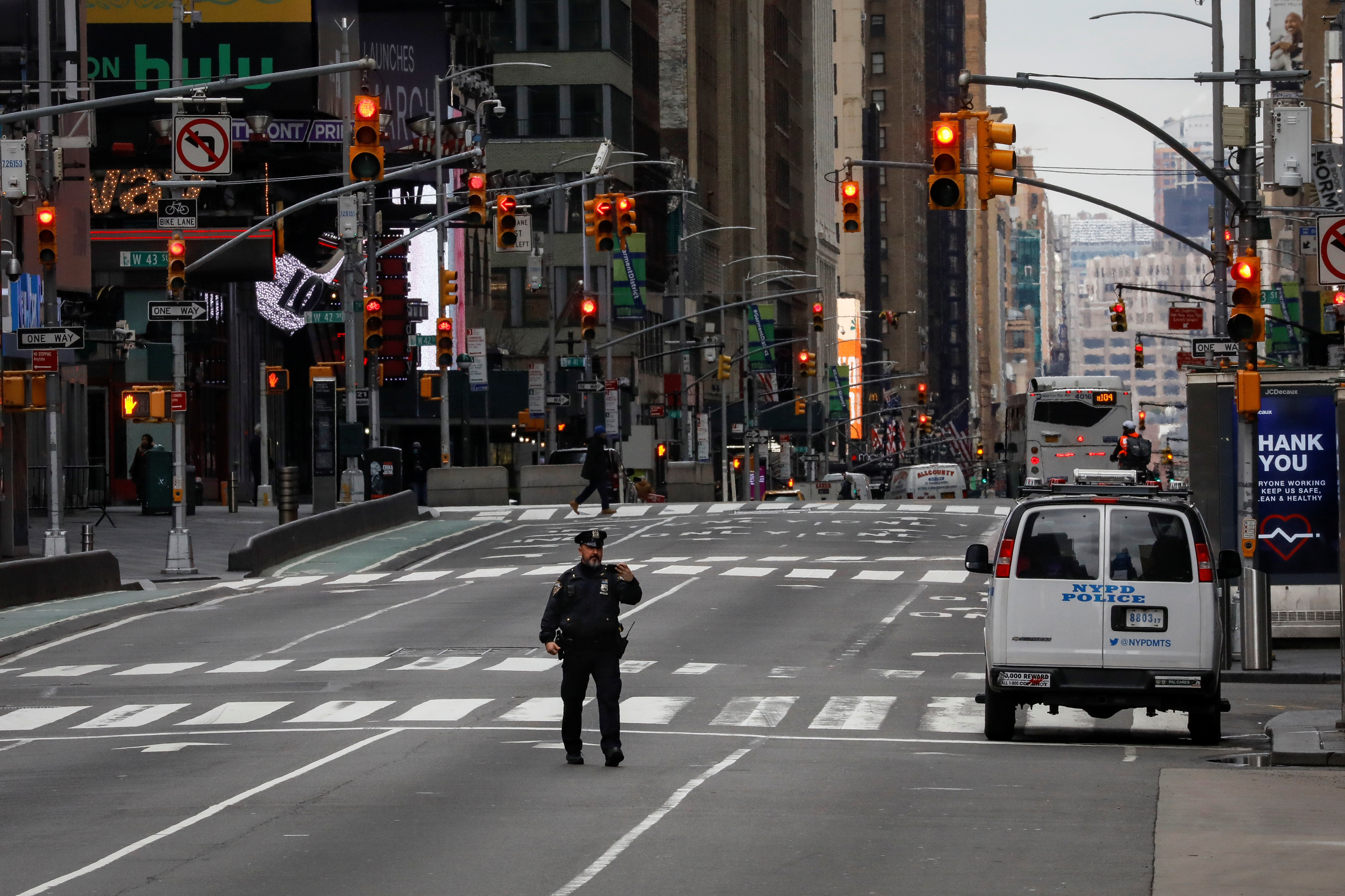 A New York City Police officer (NYPD) takes a selfie while in the middle of the street in an almost empty Times Square, during the coronavirus disease (COVID-19) outbreak, in New York City, U.S., March 31, 2020. REUTERS/Brendan McDermid     TPX IMAGES OF THE DAY - RC2GVF94Y1ID