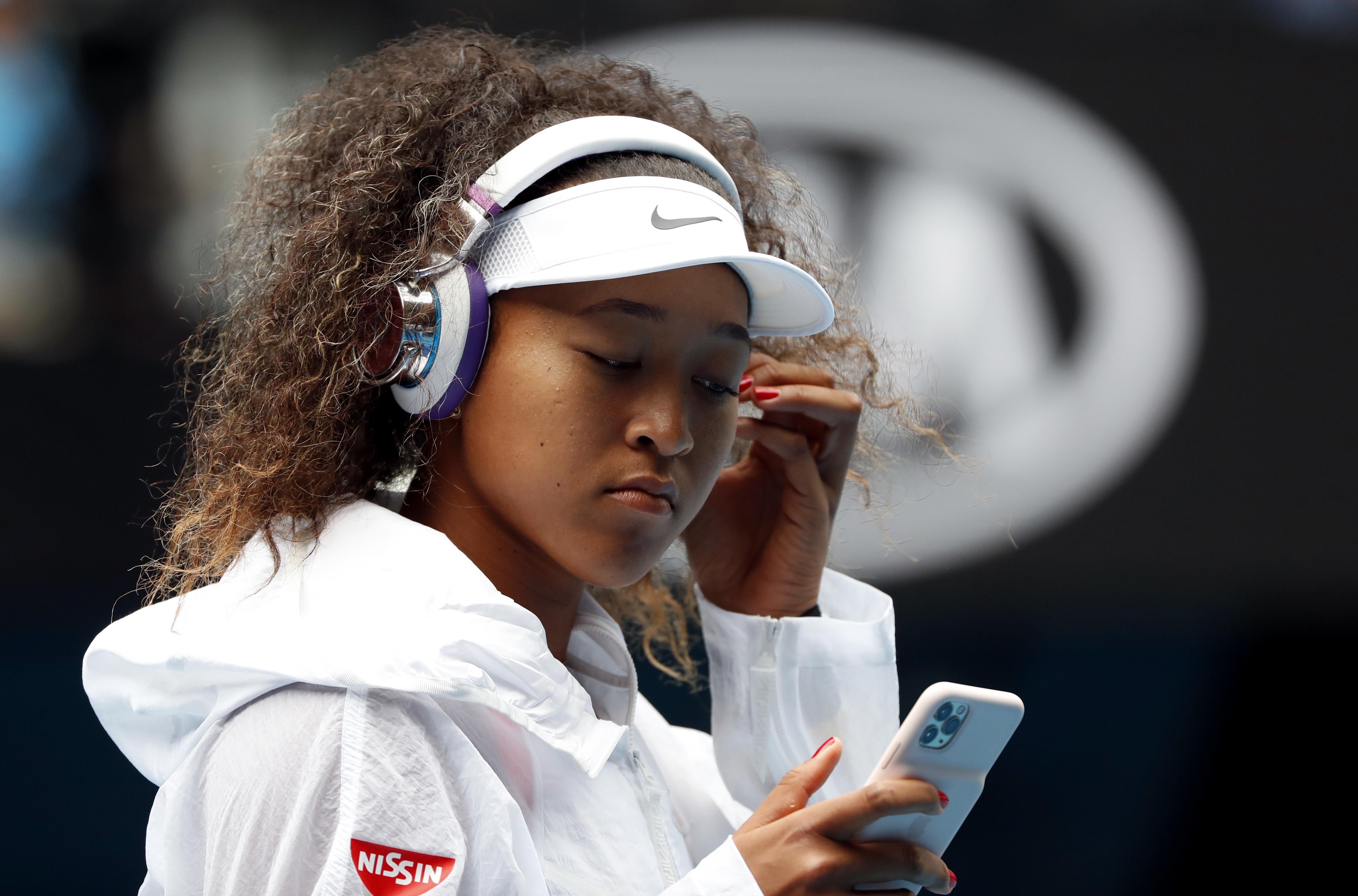 Tennis - Australian Open - First Round - Melbourne Park, Melbourne, Australia - January 20, 2020 Japan's Naomi Osaka looks at her mobile phone before her match against Czech Republic's Marie Bouzkova