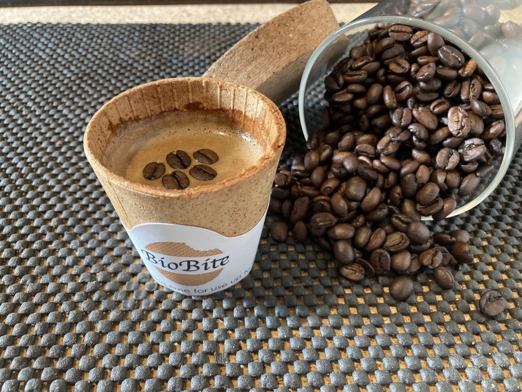An edible coffee cup with some coffee in next to a small pile of coffee beans