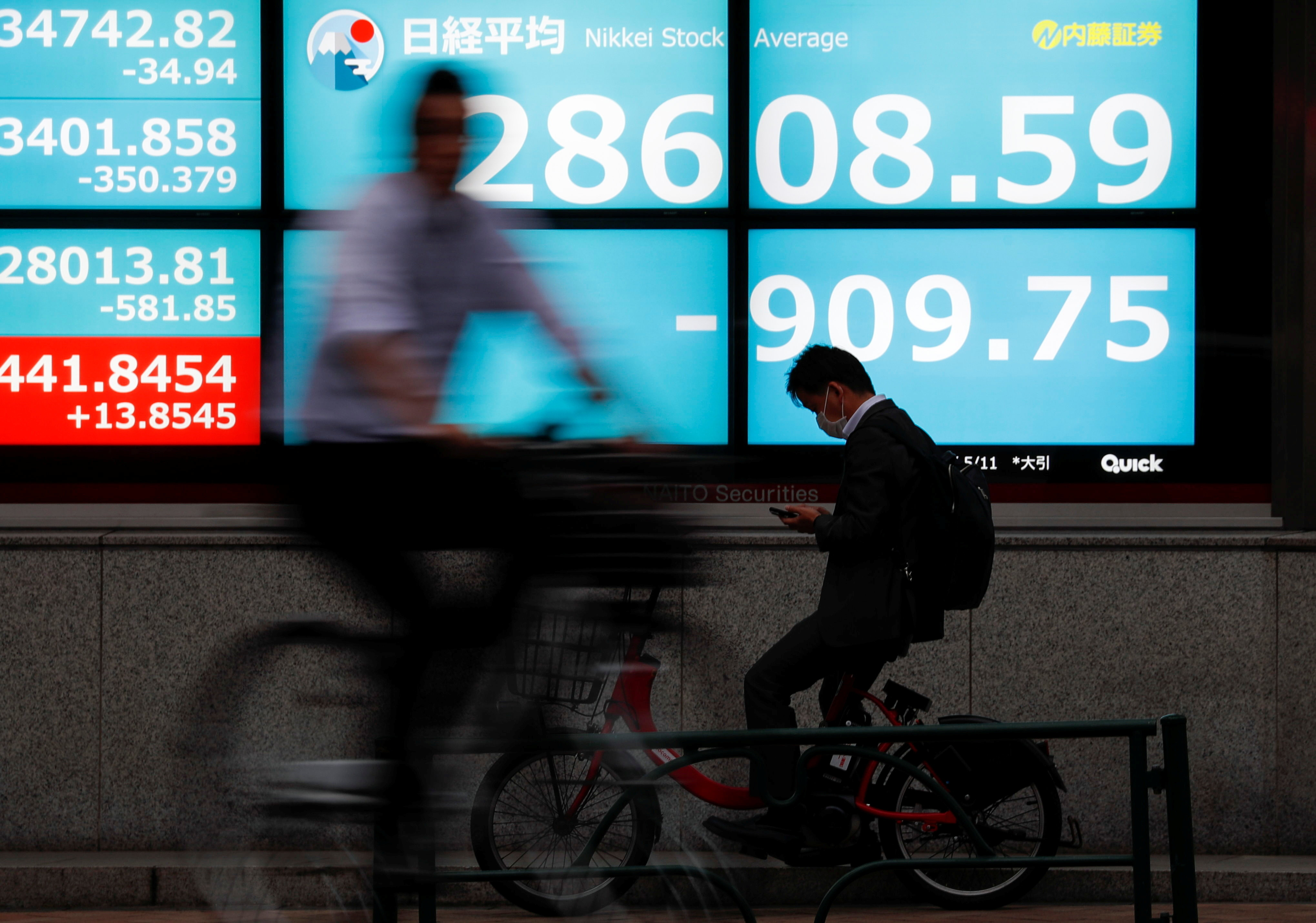 People ride bicycles past a screen displaying Nikkei share prices