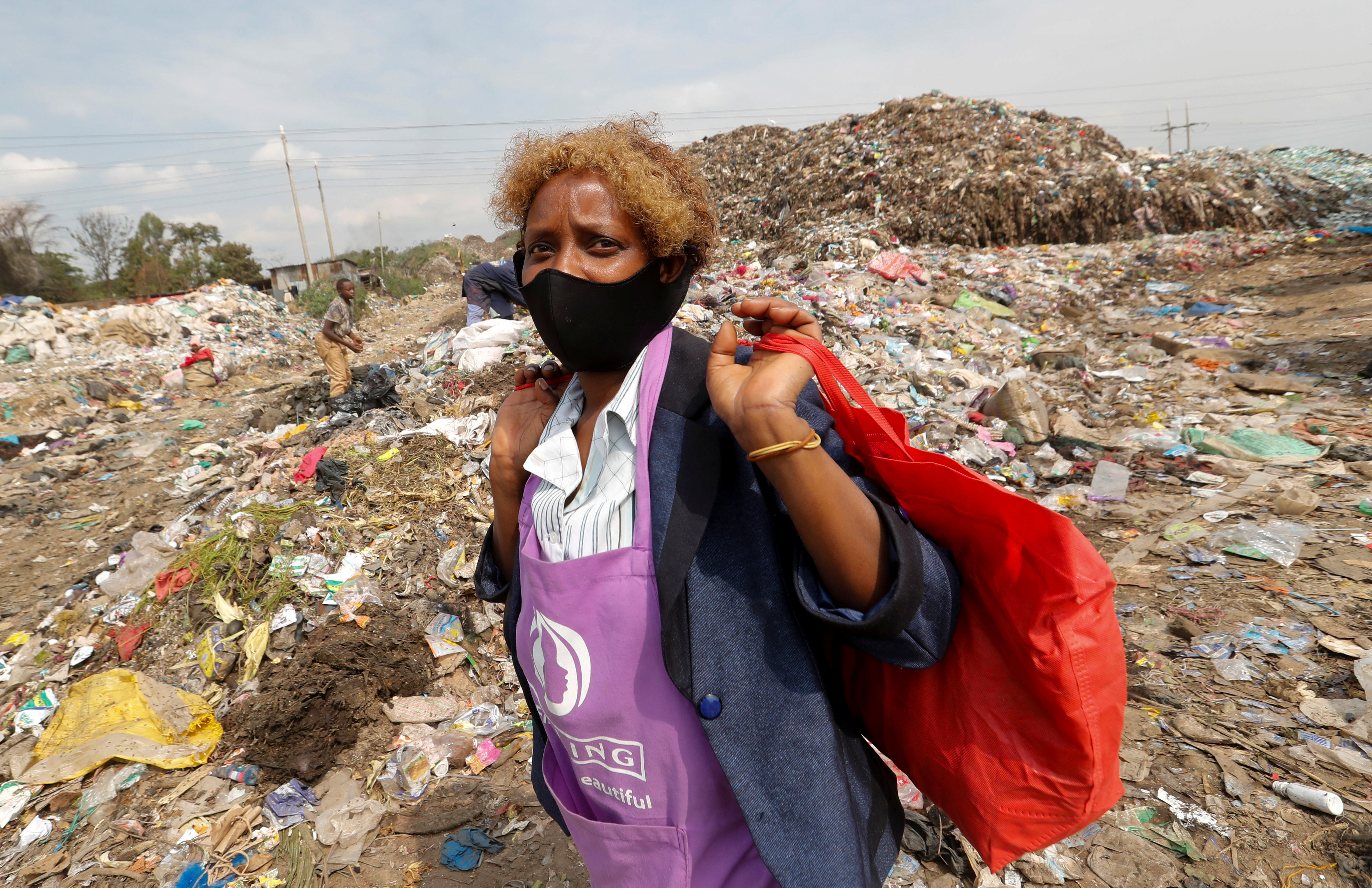 Julia Wanja, a hair stylist, carries bags of women's hair extensions to be recycled from the Dandora dumpsite, amid the coronavirus disease (COVID-19) outbreak in Eastlands Nairobi, Kenya July 29, 2020. Picture taken July 29, 2020. REUTERS/Thomas Mukoya - RC2Y6I9BUWER