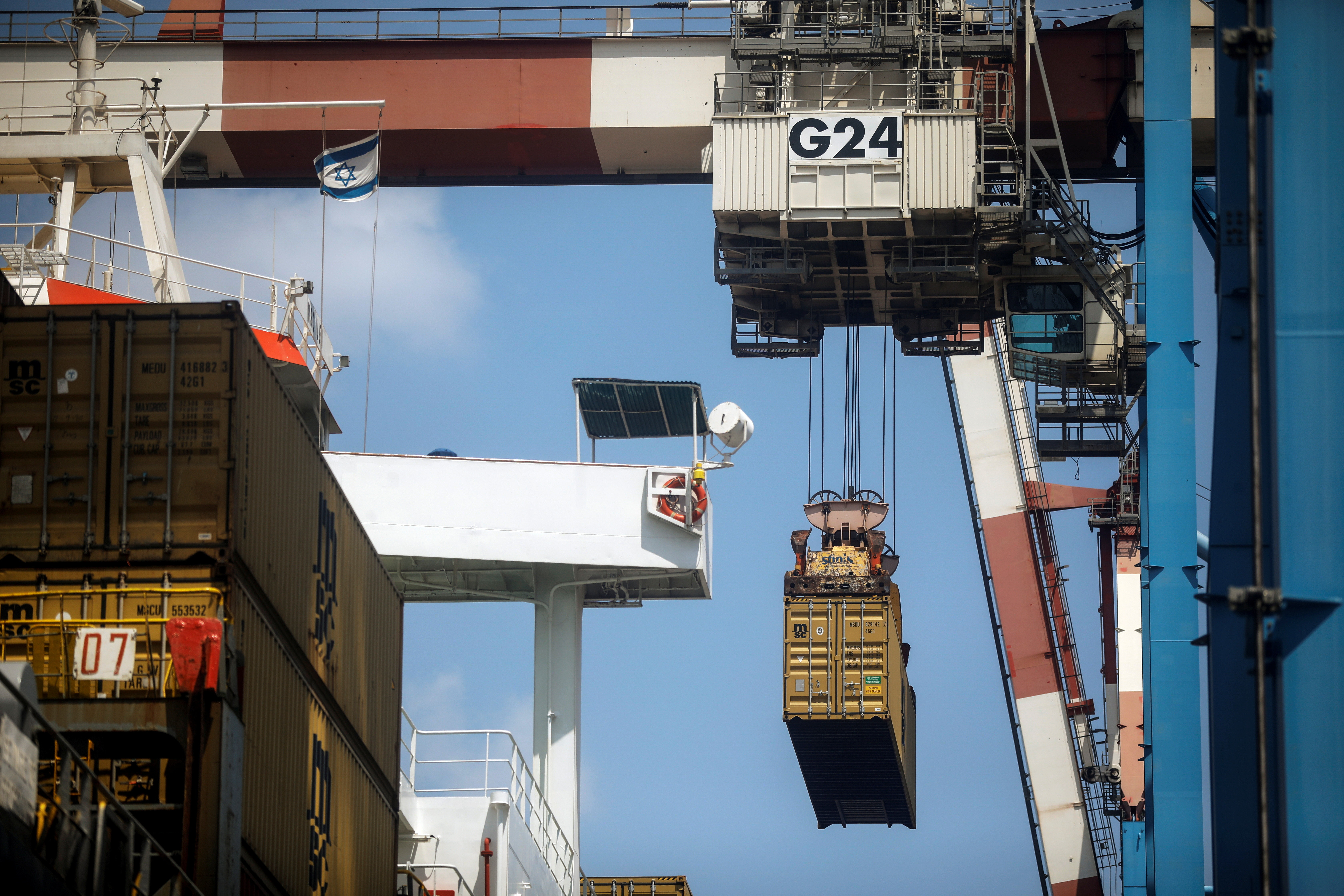 A container is being unloaded from a cargo ship while it is docked.