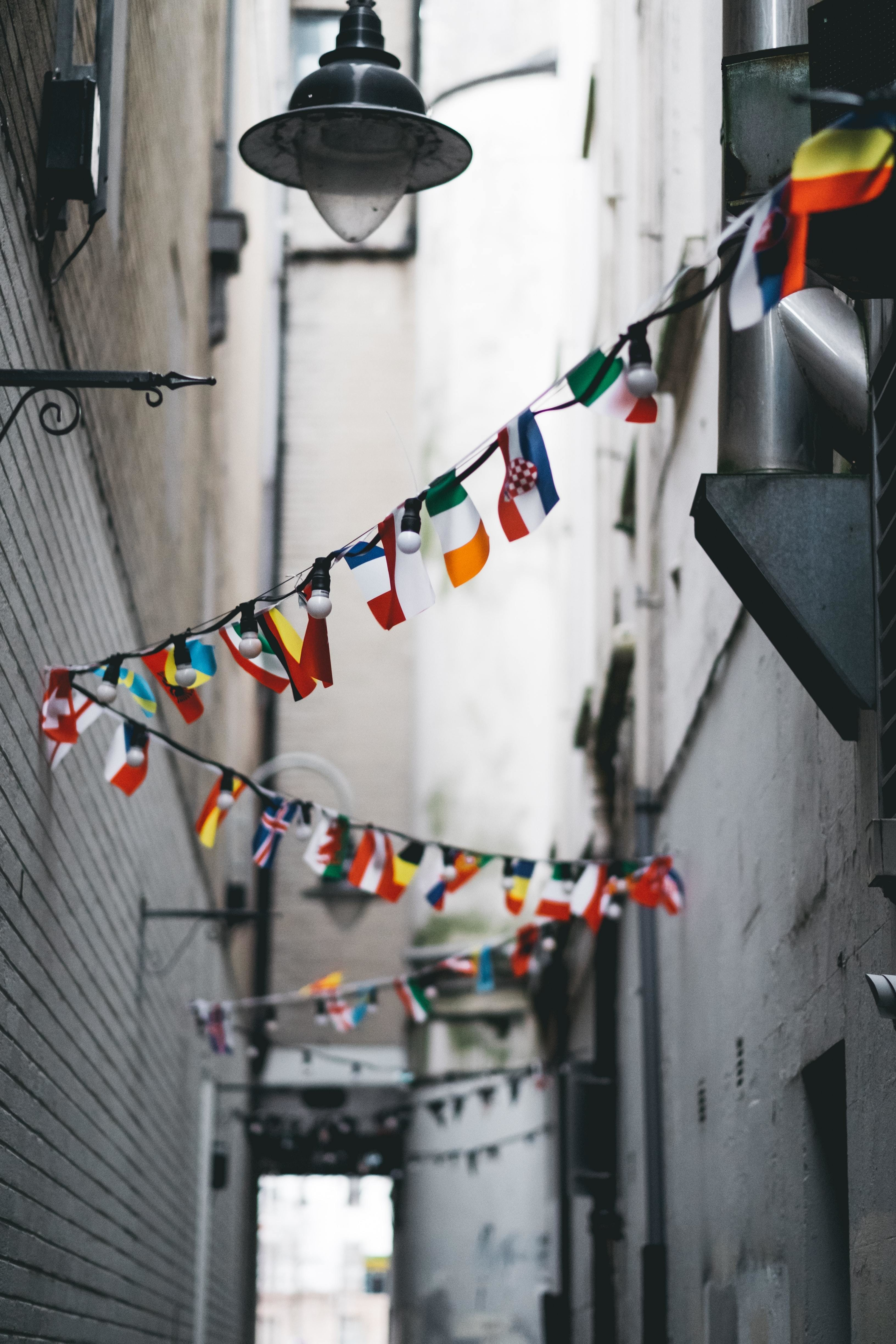 bunting hanging in an alleyway with different country flags