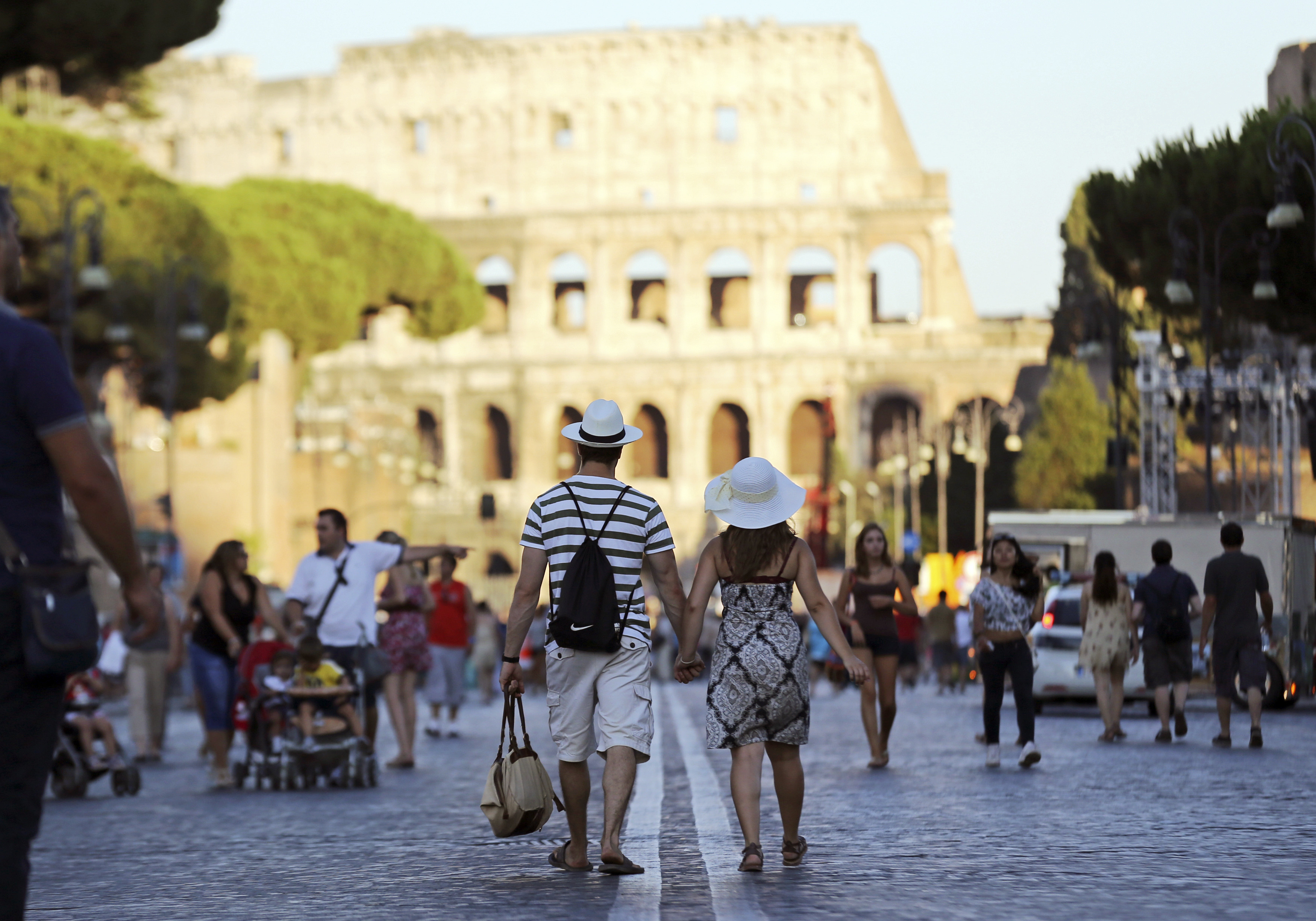 People walk at the Fori Imperiali street with Rome's famous colosseum in the background.