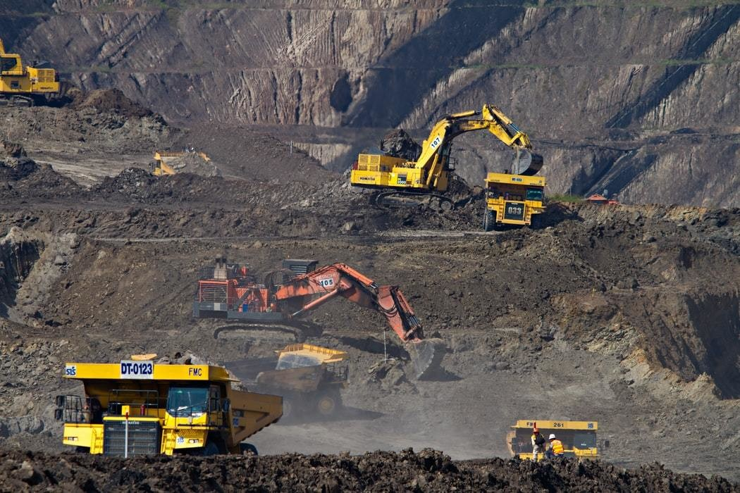 A coal mine, with 3 diggers working.