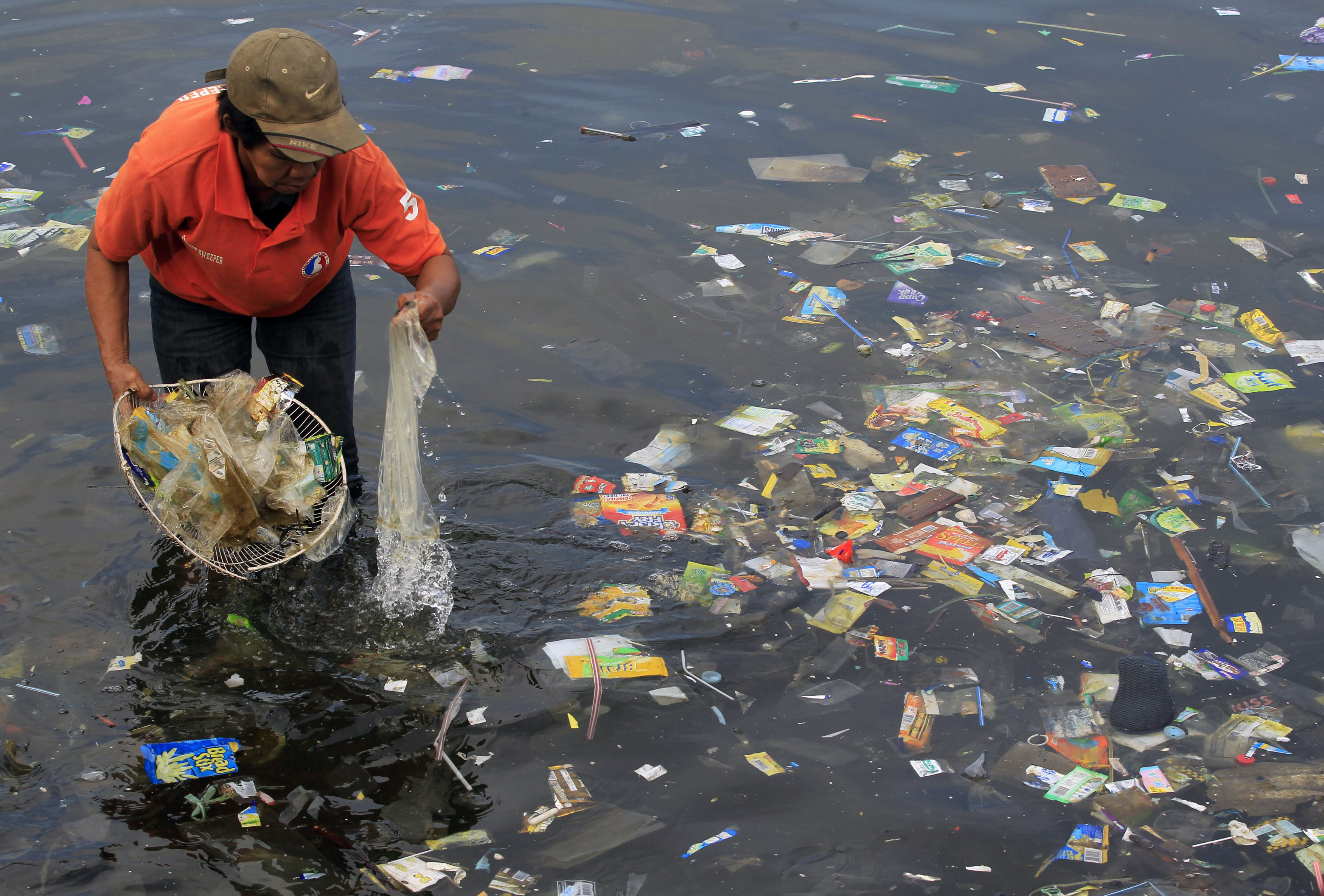 A government sanitary worker collects and segregates garbage in Manila bay
