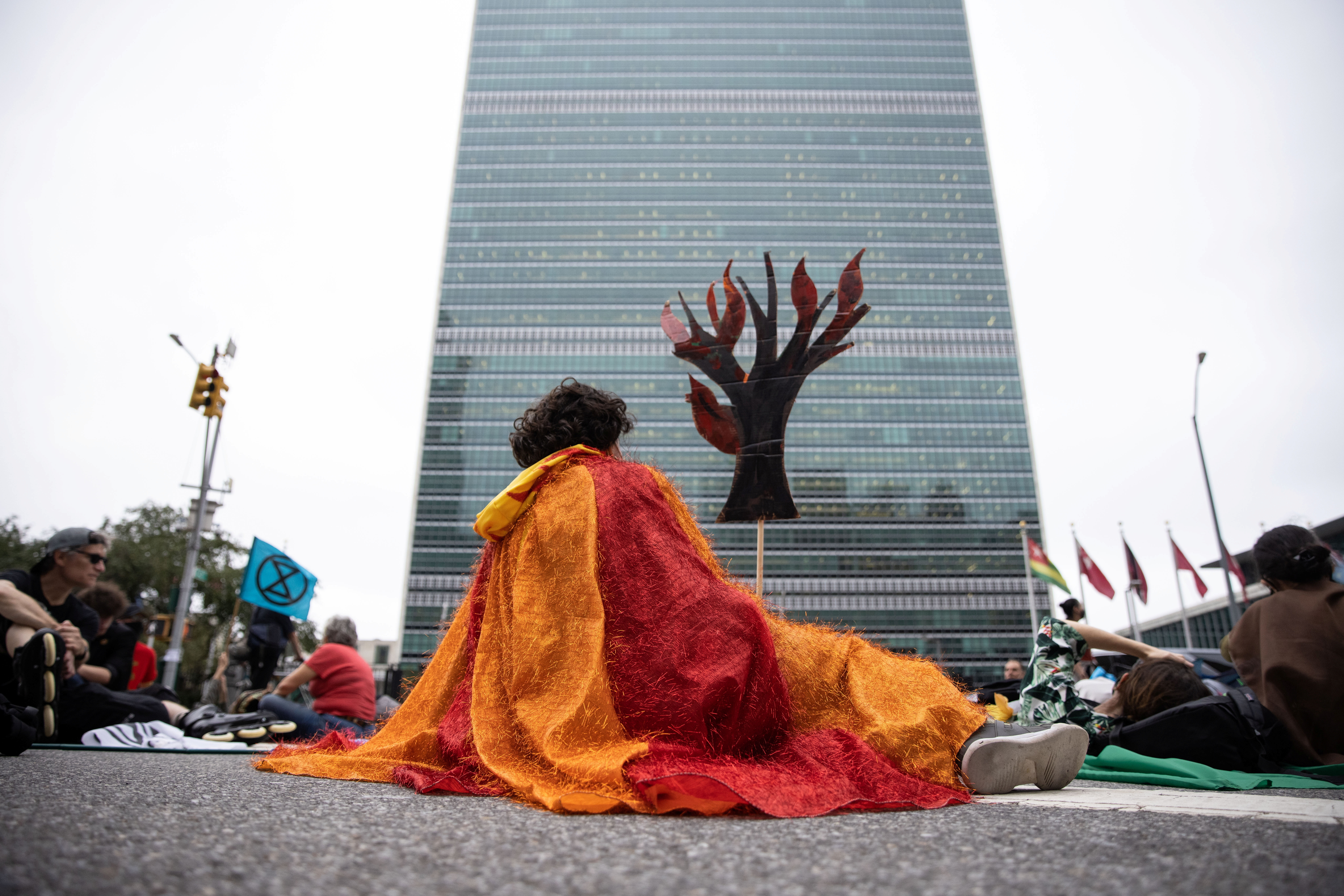 A protester holding a cardboard cut out of a tree on fire sits blocking the street in front of the United Nations during a 'non-violent resistance' climate change protest organized by Extinction Rebellion, where speakers demanded global leaders take more action before COP 26, in the Manhattan borough of New York City, U.S., September 17, 2021.