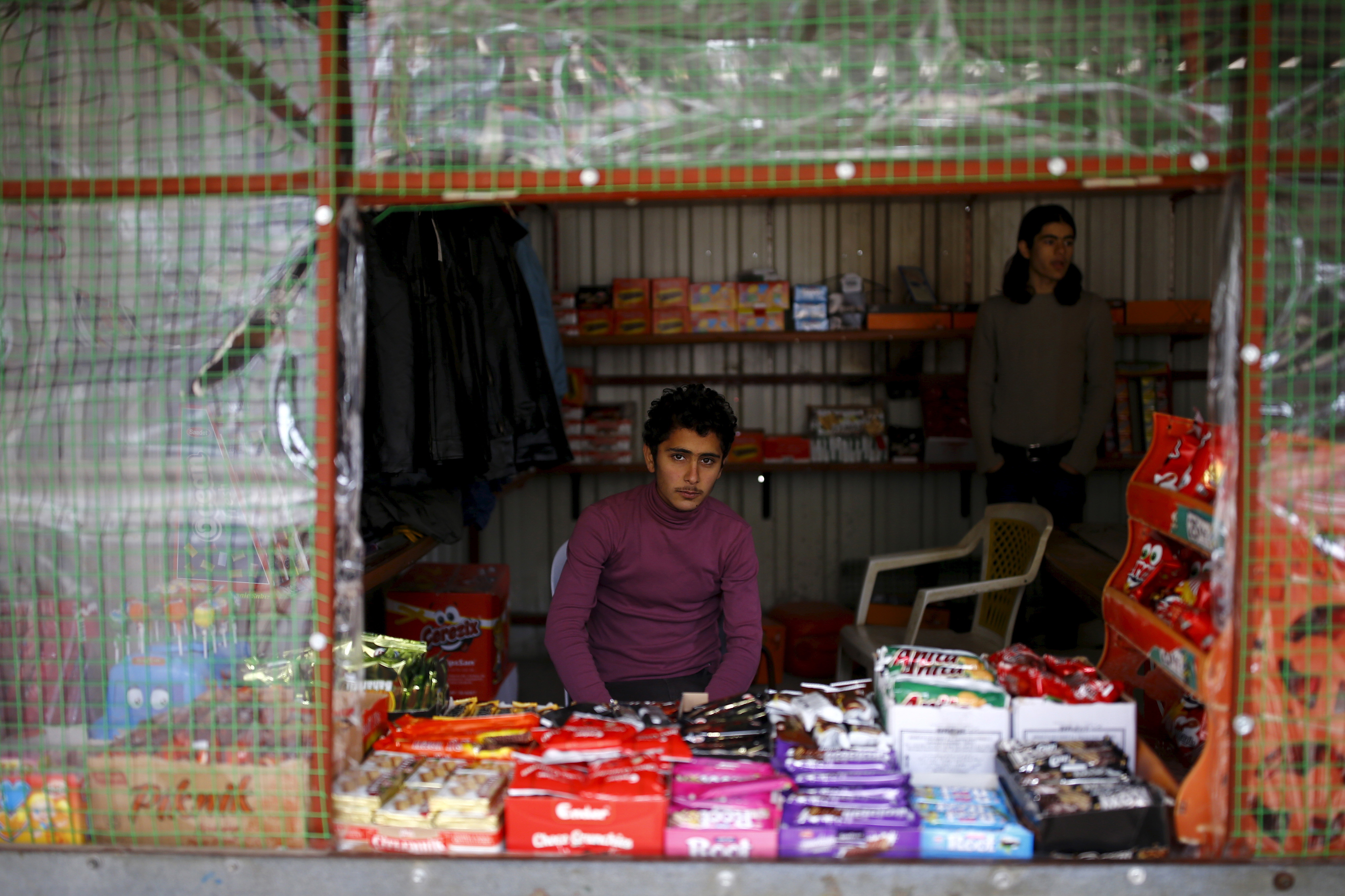 Syrian refugee Resad Bekur, 18, poses in a shop where he works in Yayladagi refugee camp in Hatay province, near the Turkish-Syrian border, Turkey, December 16, 2015. Syria's conflict has left hundreds of thousands dead, pushed millions more into exile, and had a profound effect on children who lost their homes or got caught up in the bloodletting. The drawings of young refugees living in Turkey show their memories of home and hopes for its future. The pictures also point to the mental scars borne by 2.3 million Syrian refugees living in Turkey, more than half of them children. REUTERS/Umit Bektas  - GF20000092551