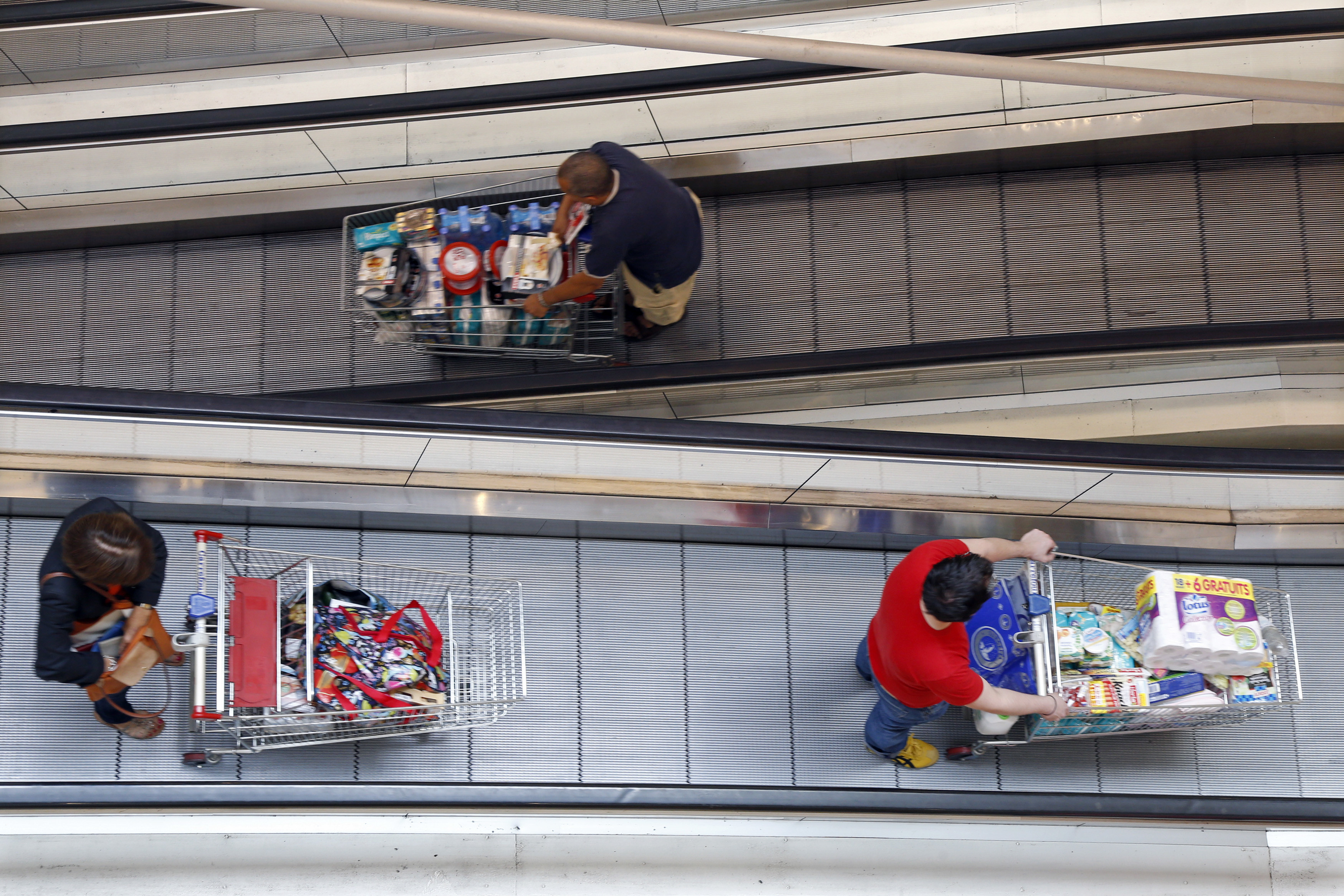 Customers push shopping trolleys on an escalator