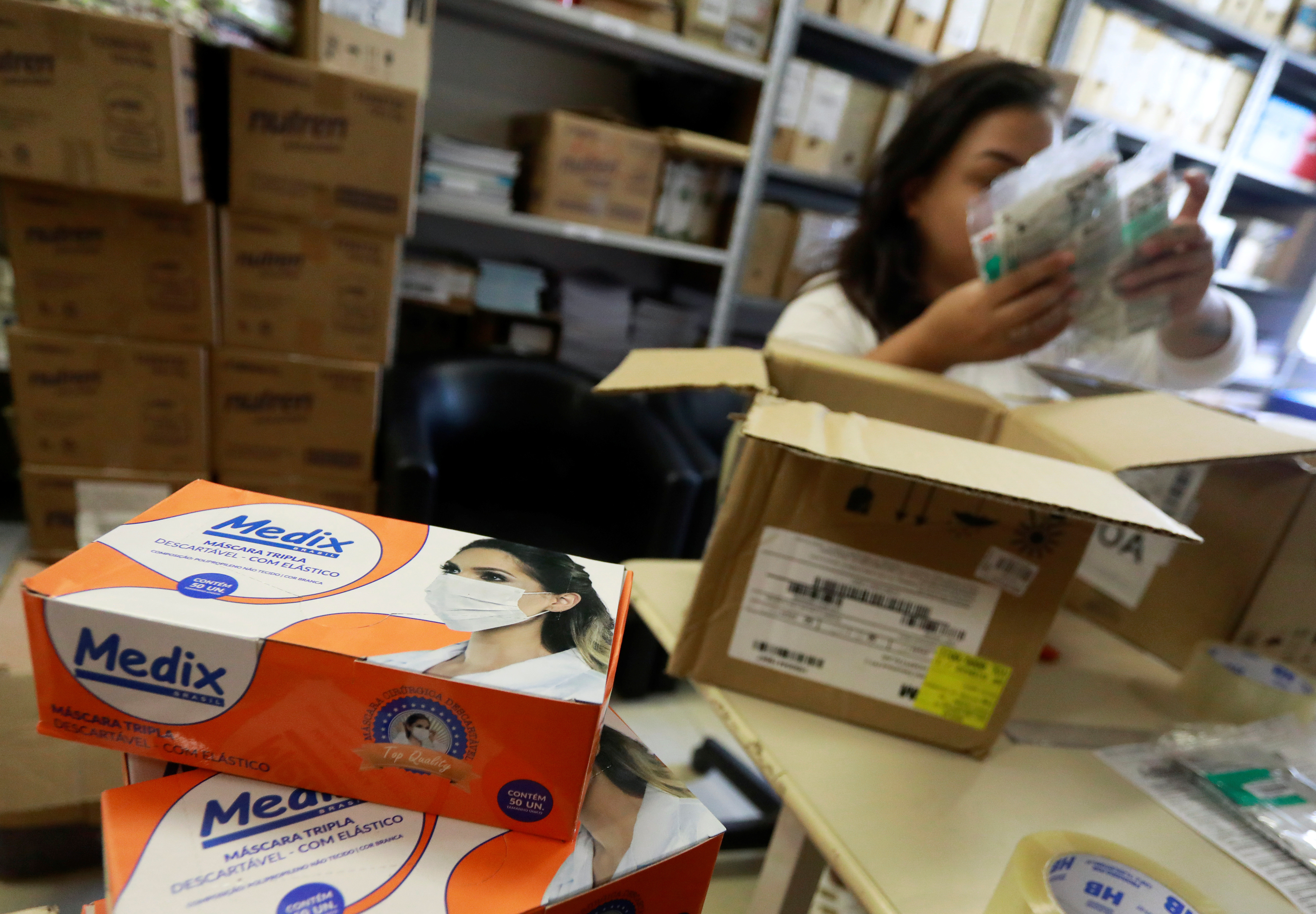 An employee packs medical masks, that are part of personal protection and survival equipment kits ordered by customers preparing against novel coronavirus, at a centre of an express delivery company in Porto Alegre, Brazil February 28, 2020. REUTERS/Diego Vara - RC2T9F9ZY8W4