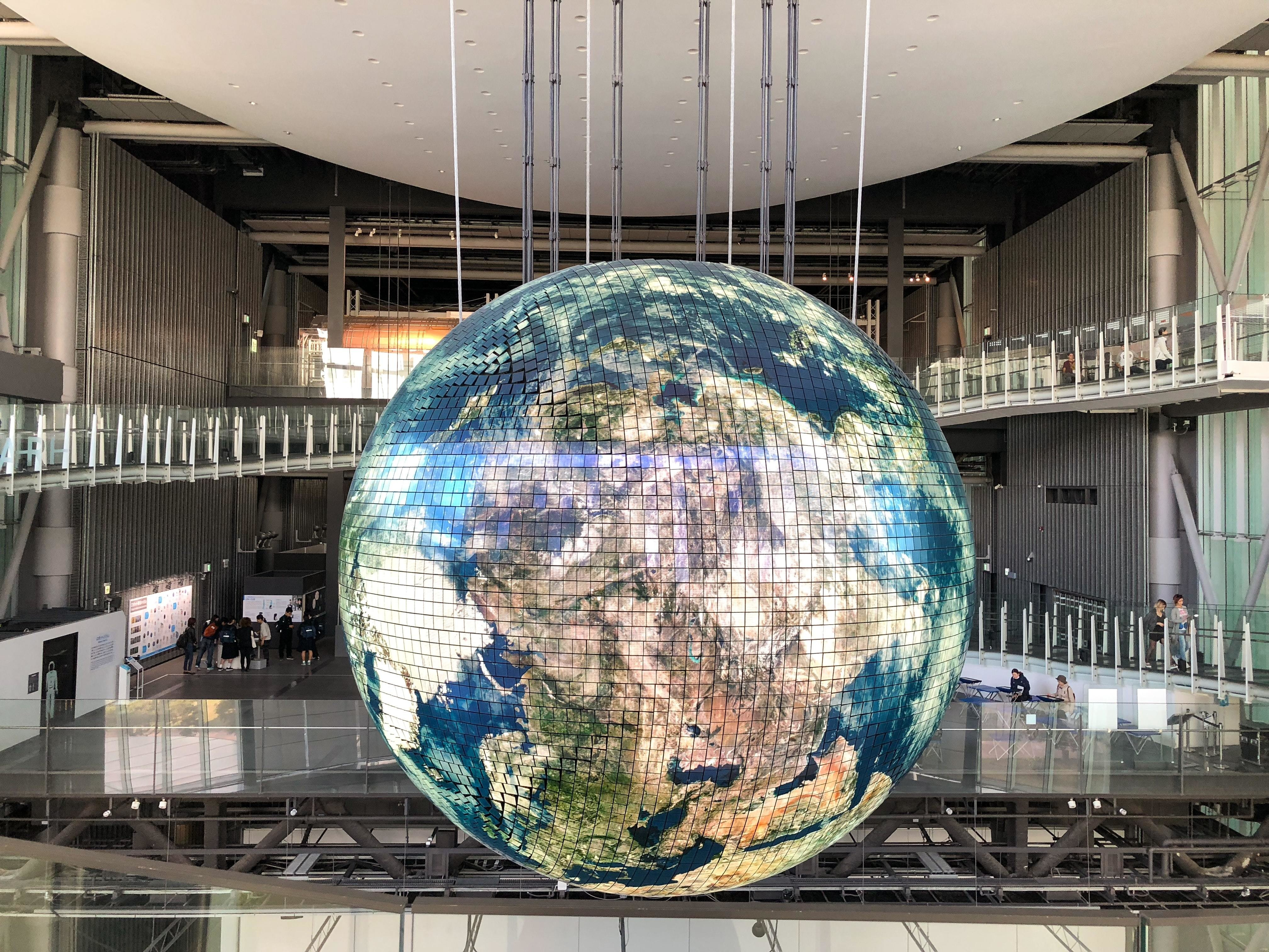 A giant Earth shaped light in a large building
