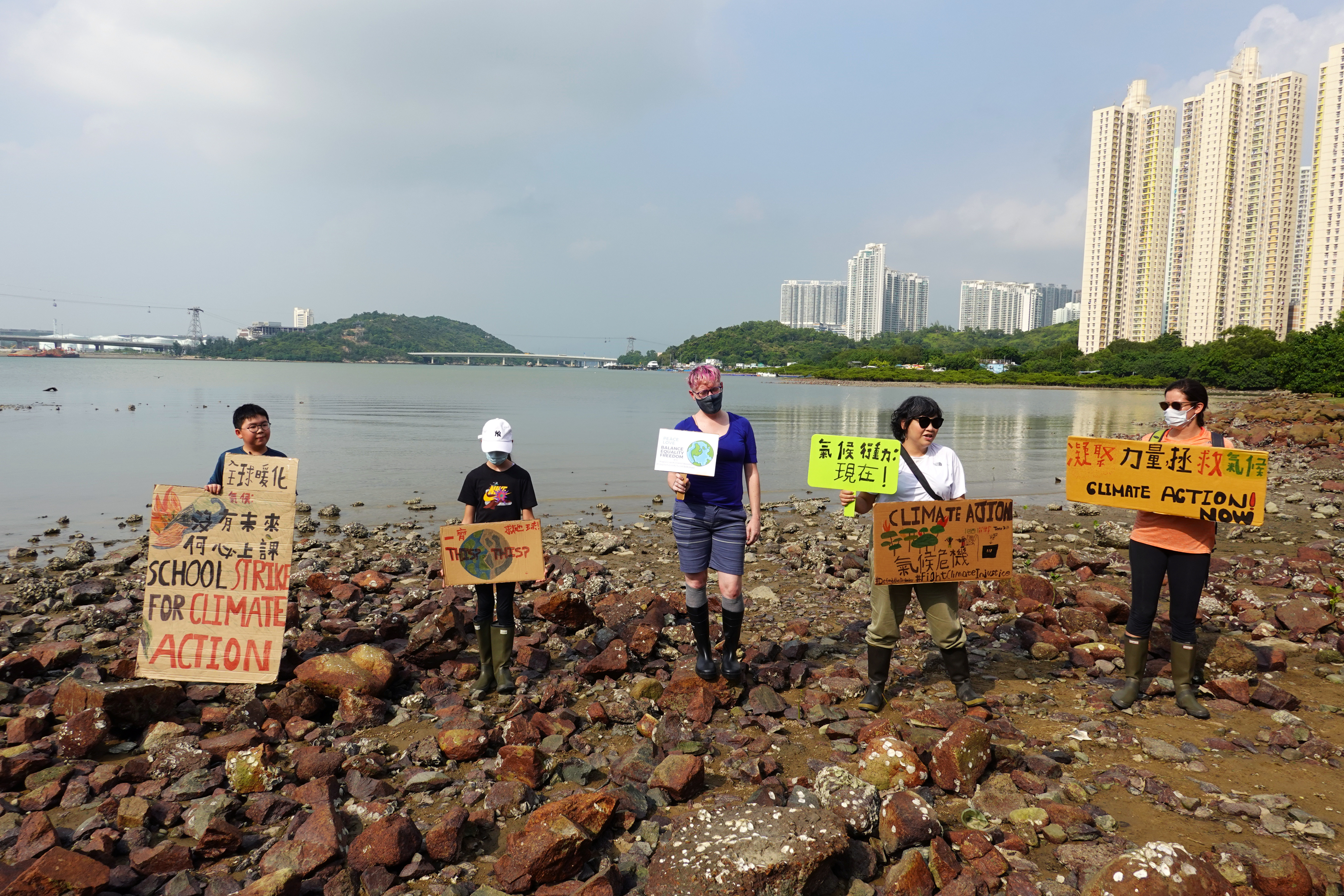 Lance Lau, 11, Elise Hon, 11, Rose Netherton, 36, and other climate activists hold placards as they pose for pictures during a climate strike and a beach clean-up at San Tau Beach on Lantau island in Hong Kong, China September 25, 2020. REUTERS/Joyce Zhou - RC2P5J9CIIMS