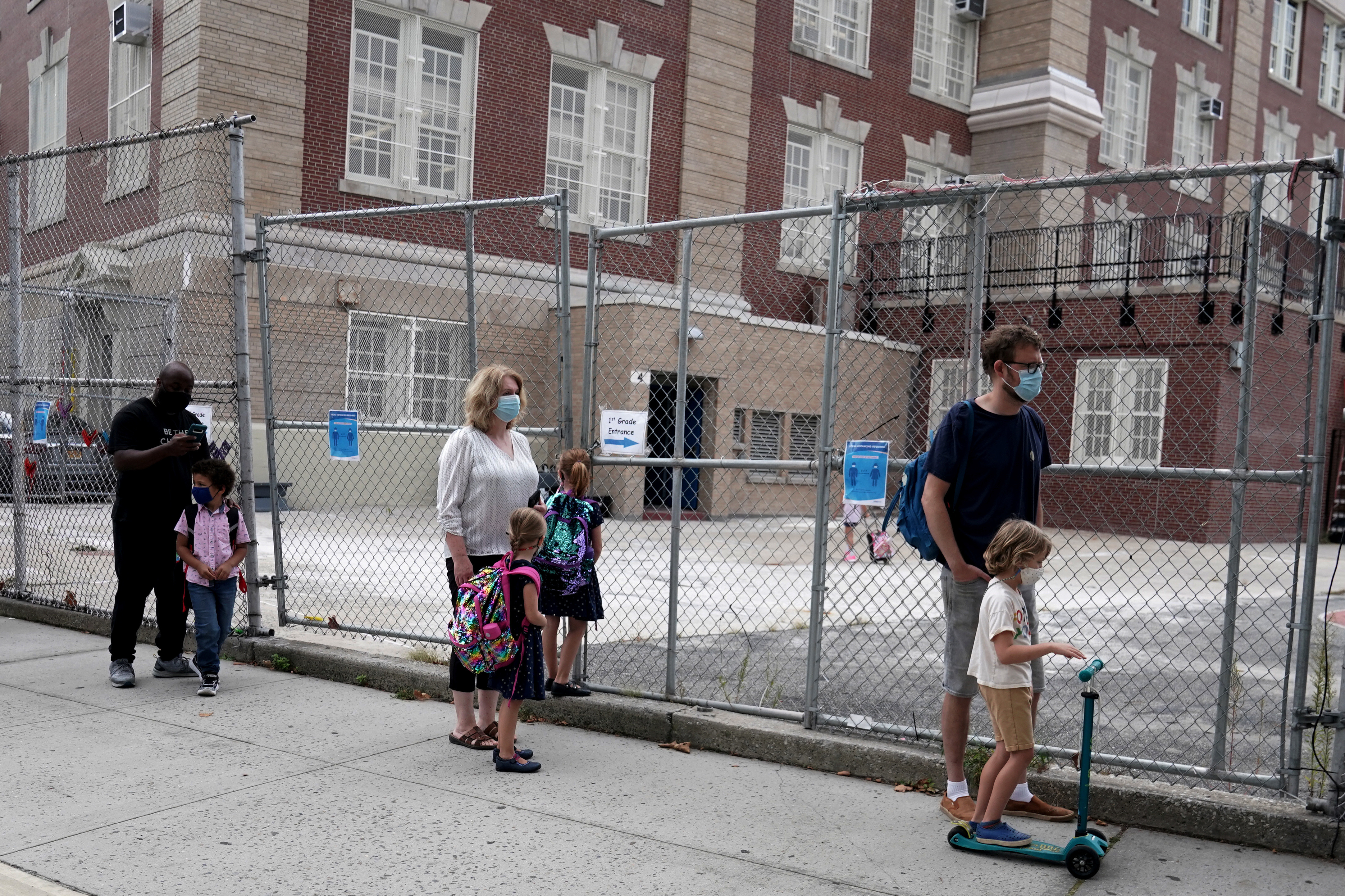 Parents line up with their children before the first day of grade 1 at P.S. 130 in the Brooklyn borough of New York City, New York, U.S., September 29, 2020.  REUTERS/Carlo Allegri - RC2E8J9V7UOC