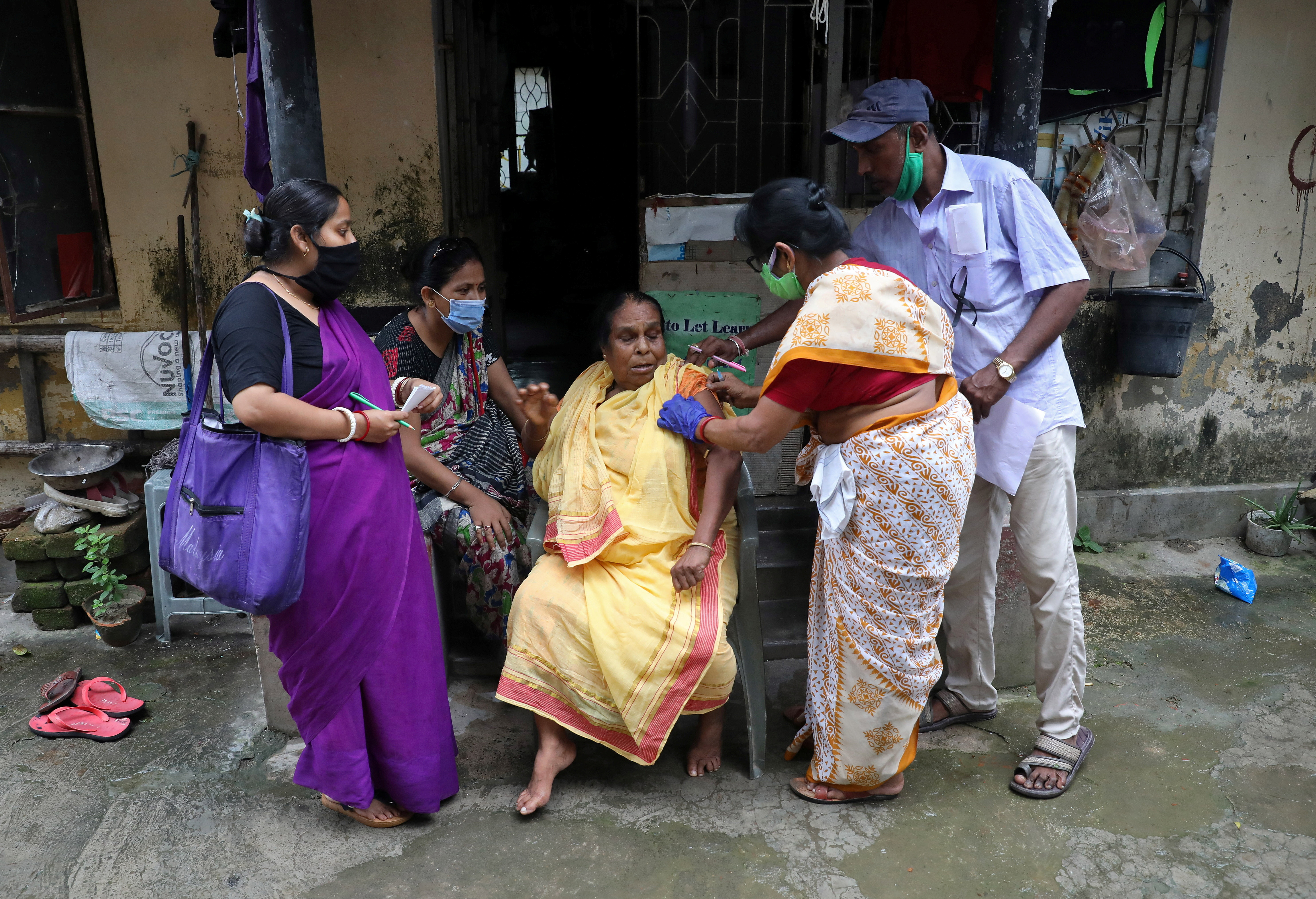 Rekha Ghosh, 64, reacts a she receives a dose of COVISHIELD, a coronavirus disease vaccine manufactured by Serum Institute of India, outside her house during a door-to-door vaccination drive in Kolkata, India, August 12, 2021. REUTERS/Rupak De Chowdhuri - RC2L3P9PCKR5