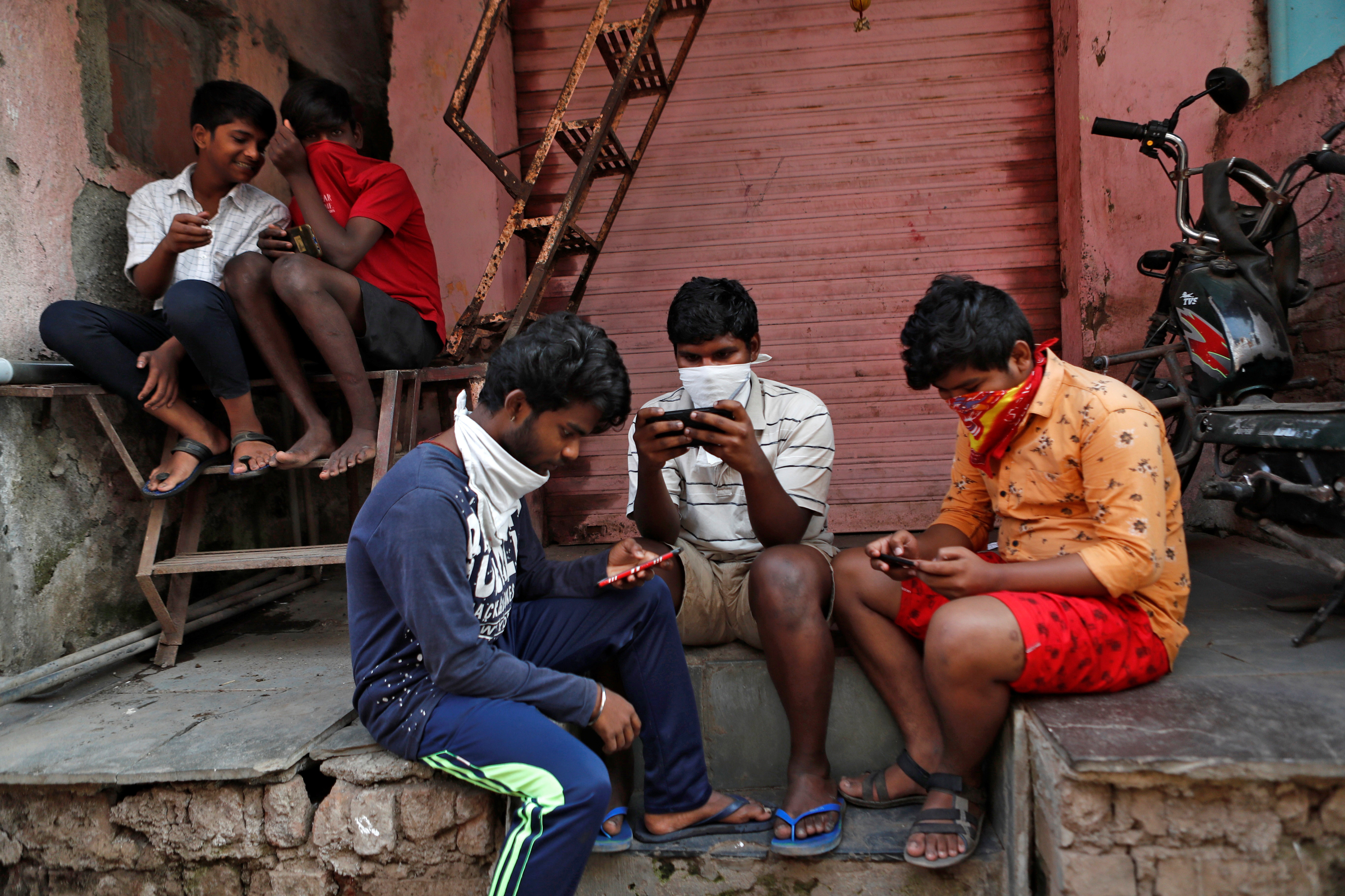 "A group of boys look at their mobile phones, during a nationwide lockdown in India to slow the spread COVID-19, in Dharavi, one of Asia's largest slums, during the coronavirus disease outbreak, in Mumbai, India, April 9, 2020. REUTERS/Francis Mascarenhas      SEARCH ""CORONAVIRUS MUMBAI SLUM"" FOR THIS STORY. SEARCH ""WIDER IMAGE"" FOR ALL STORIES. - RC2Z7G9QKZ3D"
