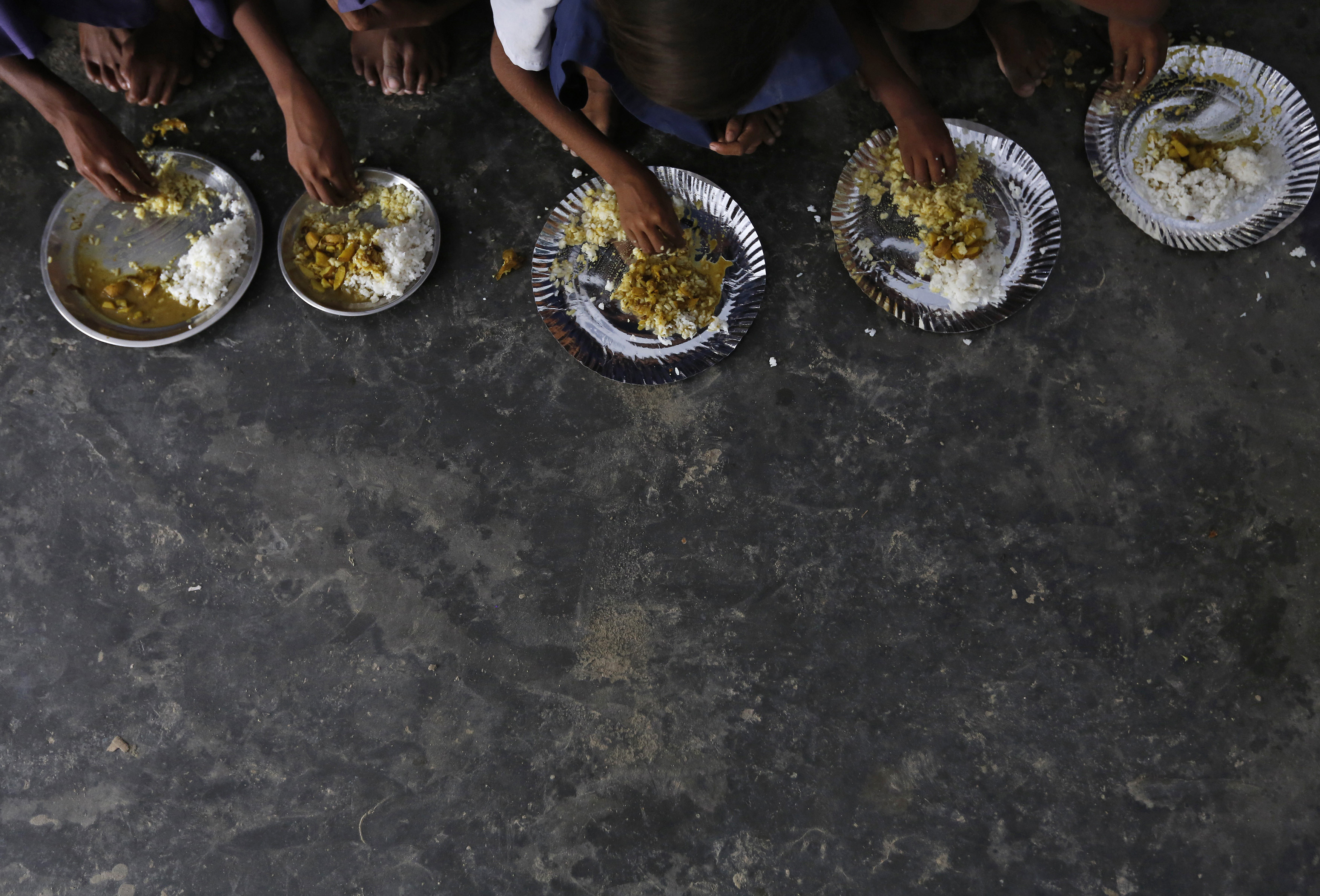 Schoolchildren eat their free mid-day meal