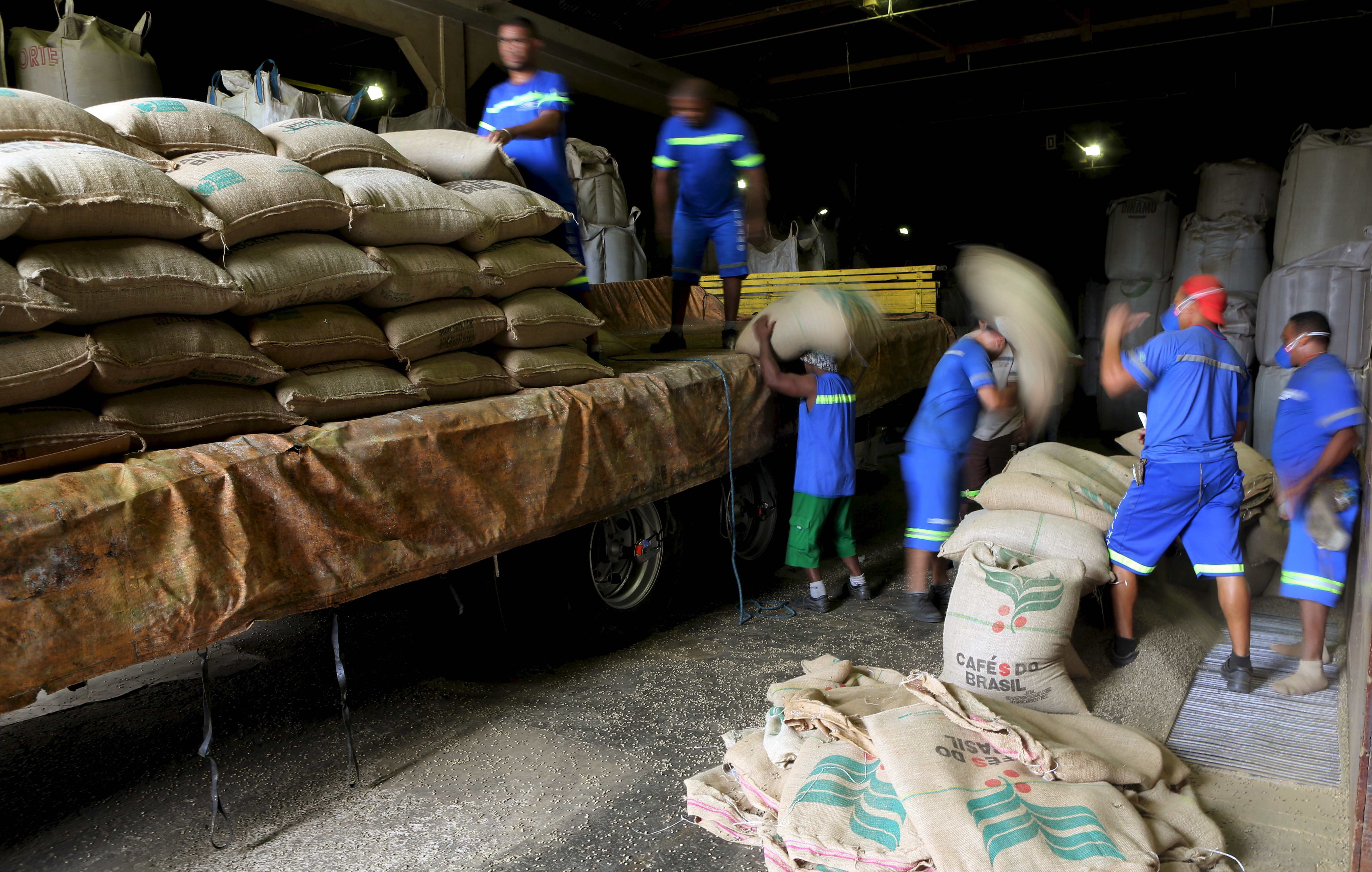 workers unload large canvass sacks filled with coffee beans